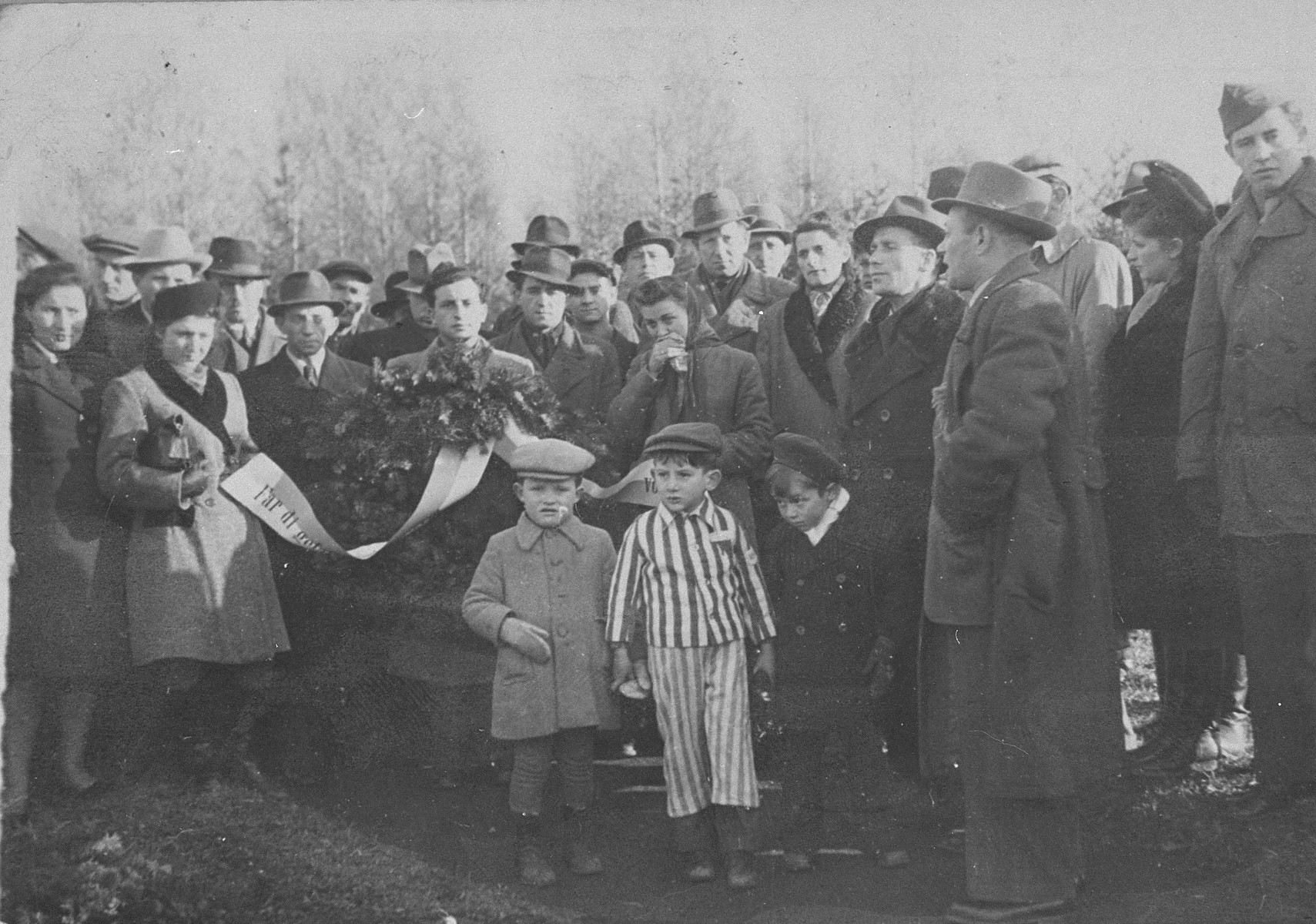 Jewish DPs attend a memorial service in the Buchenwald concentration camp.    The little boy in the concentration camp uniform may be Joseph Schleifstein. The little boy in the beige coat and hat has been idenitifed as Lawrence Swern (Cwern). Jack Borenstein is the man standing behind Lawrence Swern.