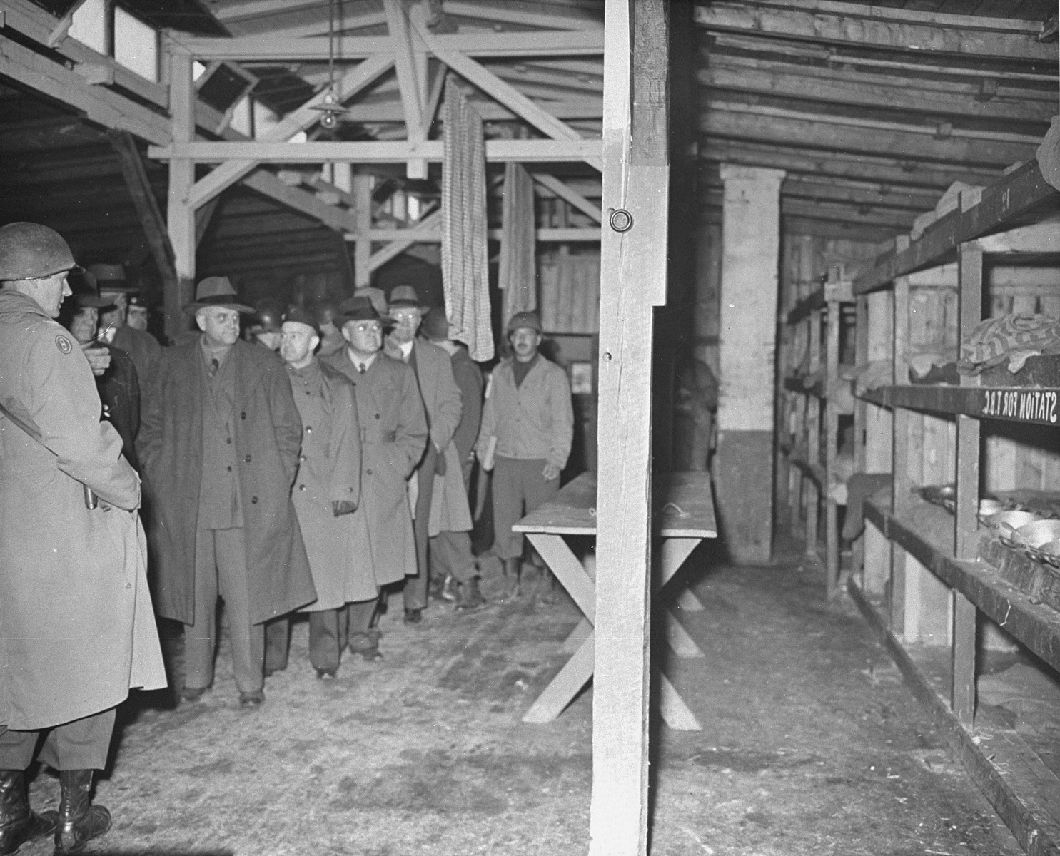 Members of a U.S. Congressional committee investigating Nazi atrocities walk through a prisoner barracks in the newly liberated Buchenwald concentration camp.