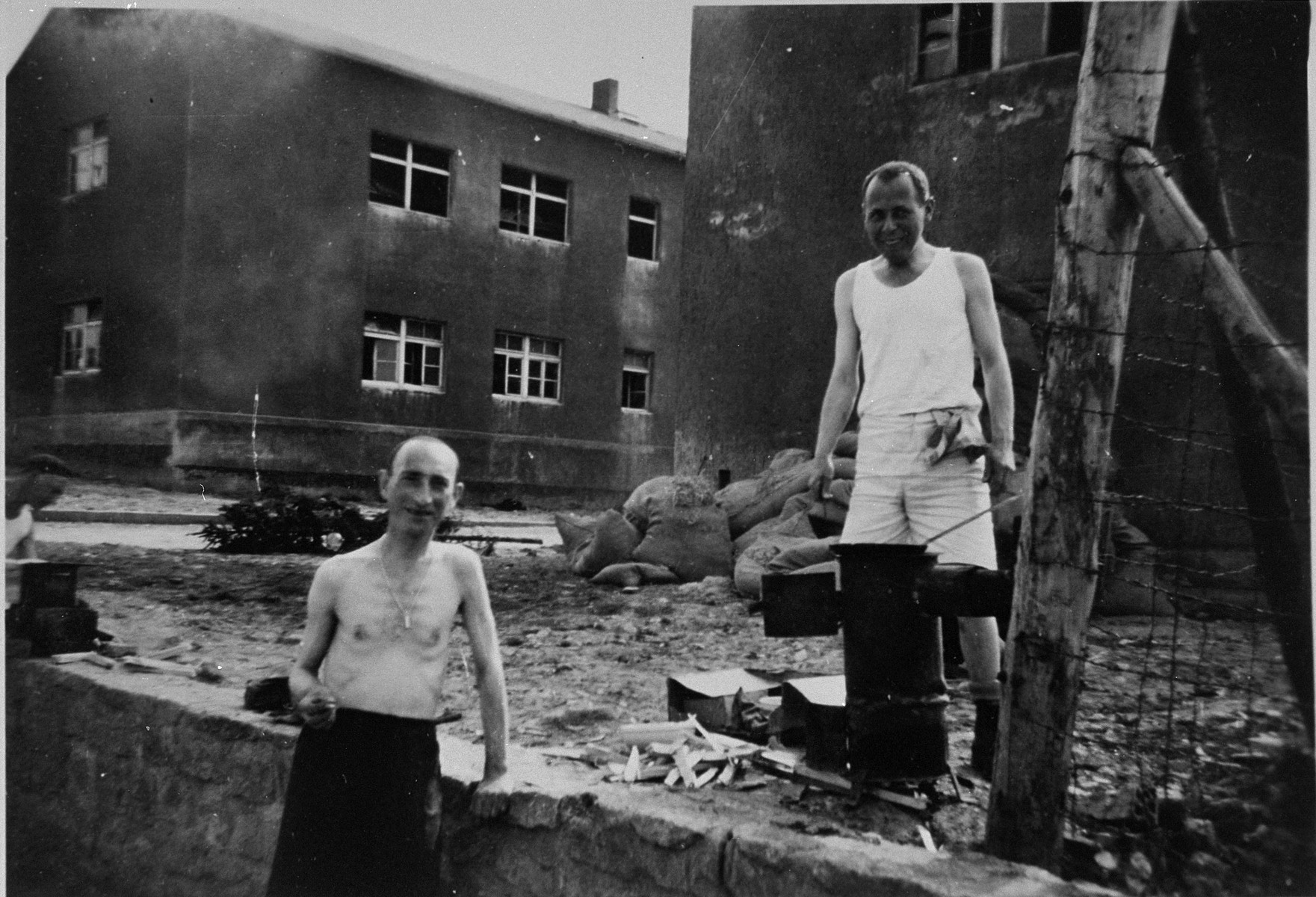 "Two Buchnewald survivors in Buchenwald prepare a meal after liberation.    The inscription on the back of the photograph reads, ""Buchenwald Prison Camp Inmates.  5/7/45.  Man on left from Antwerp weighed 90 kilos (180 lbs) on entry to camp.  When picture was taken weighed 40 kilos (80 lbs.)."