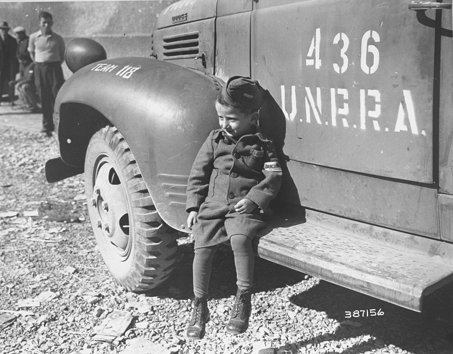 Joseph Schleifstein, a four-year-old survivor of Buchenwald, sits on the running board of an UNRRA truck soon after the liberation of the camp.