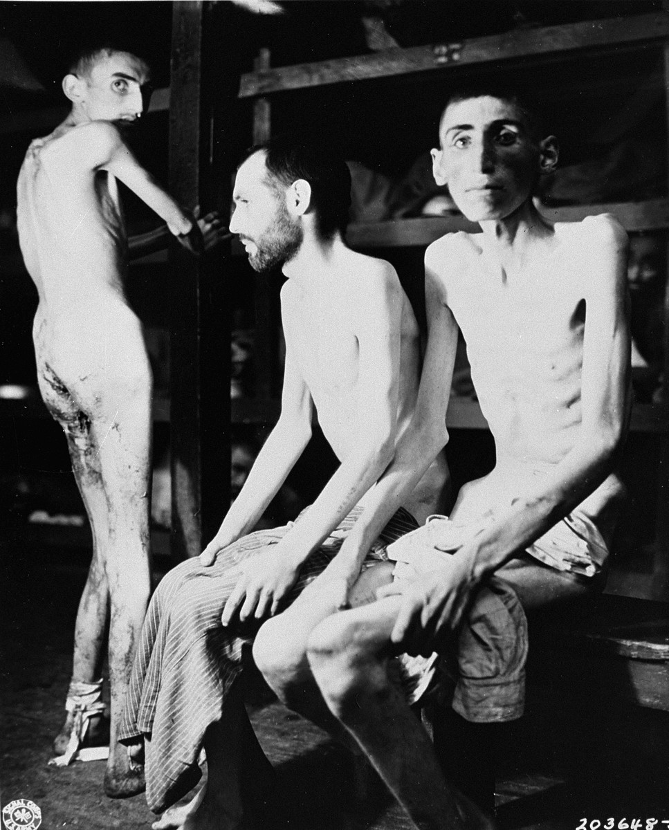 Three emaciated survivors in a barracks in the newly liberated Buchenwald concentration camp.