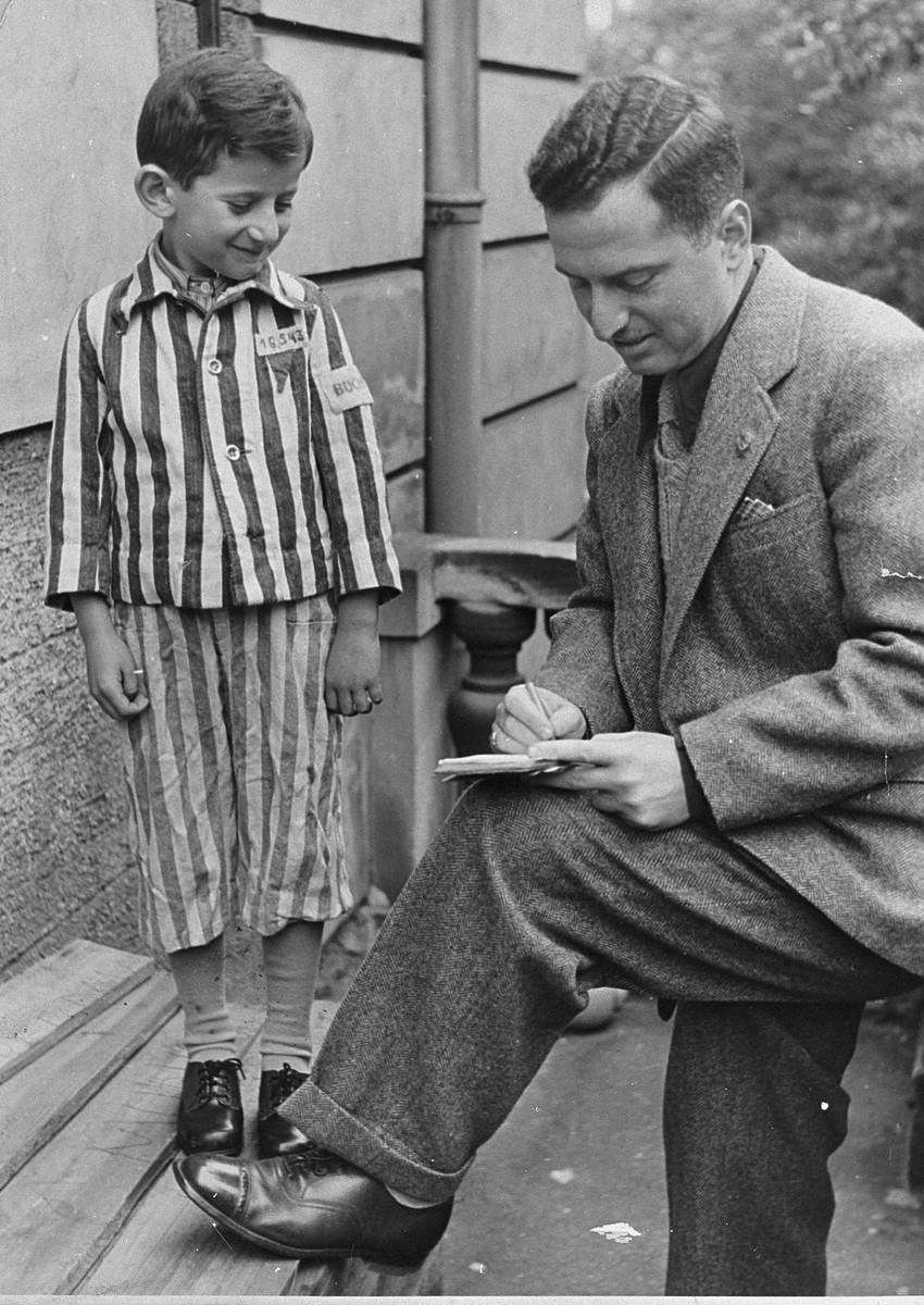 Joseph Schleifstein, wearing his old Buchenwald uniform, is interviewed by a journalist.