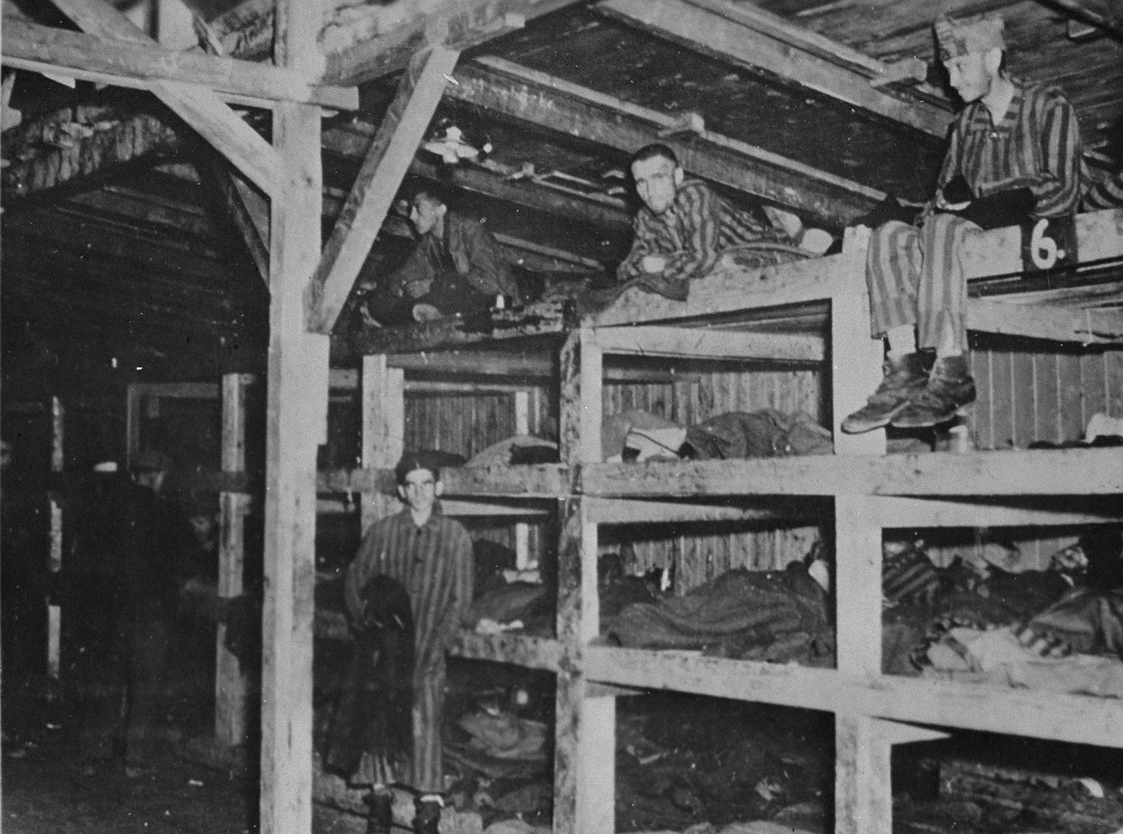Survivors sit in multi-tiered bunks in a barracks in the newly liberated Buchenwald concentration camp.
