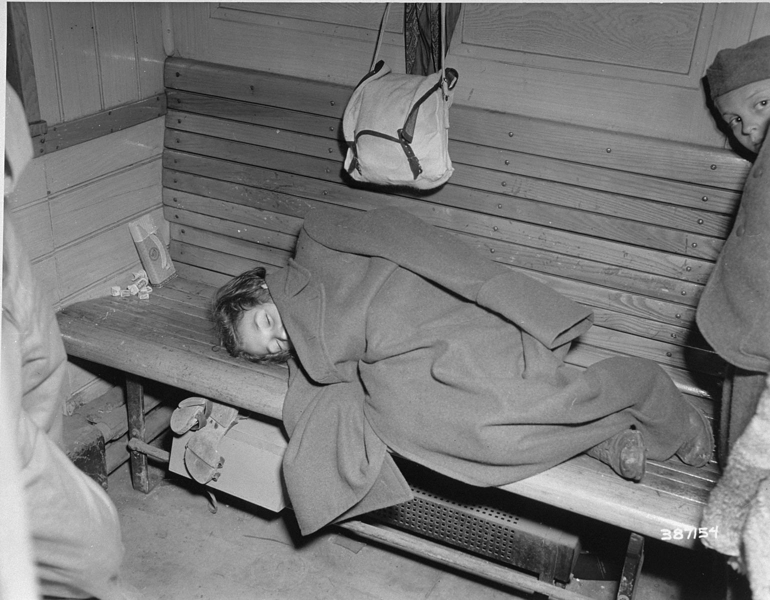"""A Jewish girl liberated in Buchenwald sleeps during the train ride from the camp to France.    The original caption reads, """"A tired little Jewish girl takes a nap on a wooden bench in the evacuation train that is taking her and other Jewish children from the Buchenwald concentration camp to France.  From there, some will be sent to Palestine, others to America."""""""
