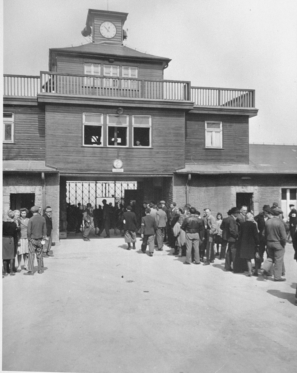 Visiting radio commentators, on an official tour of the war front, wait at the entrance to newly liberated Buchenwald concentration camp.