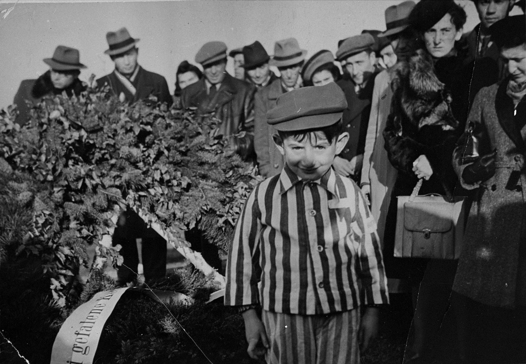 Dressed in his former concentration camp uniform, the Jewish DP child Joseph Schleifstein attends a memorial service in Buchenwald.