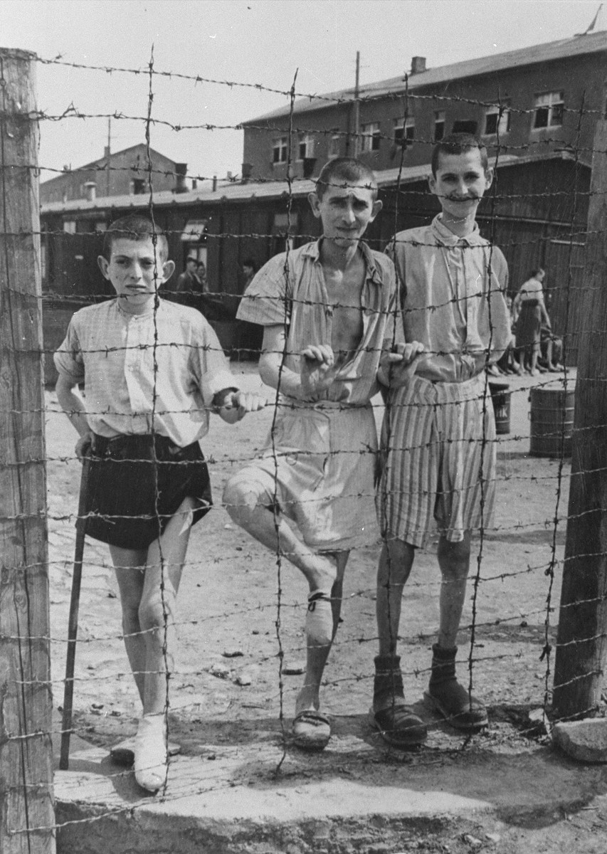 Young survivors behind a barbed wire fence in Buchenwald concentration camp.   Among those pictured is Abram Zylbersztajn (middle).