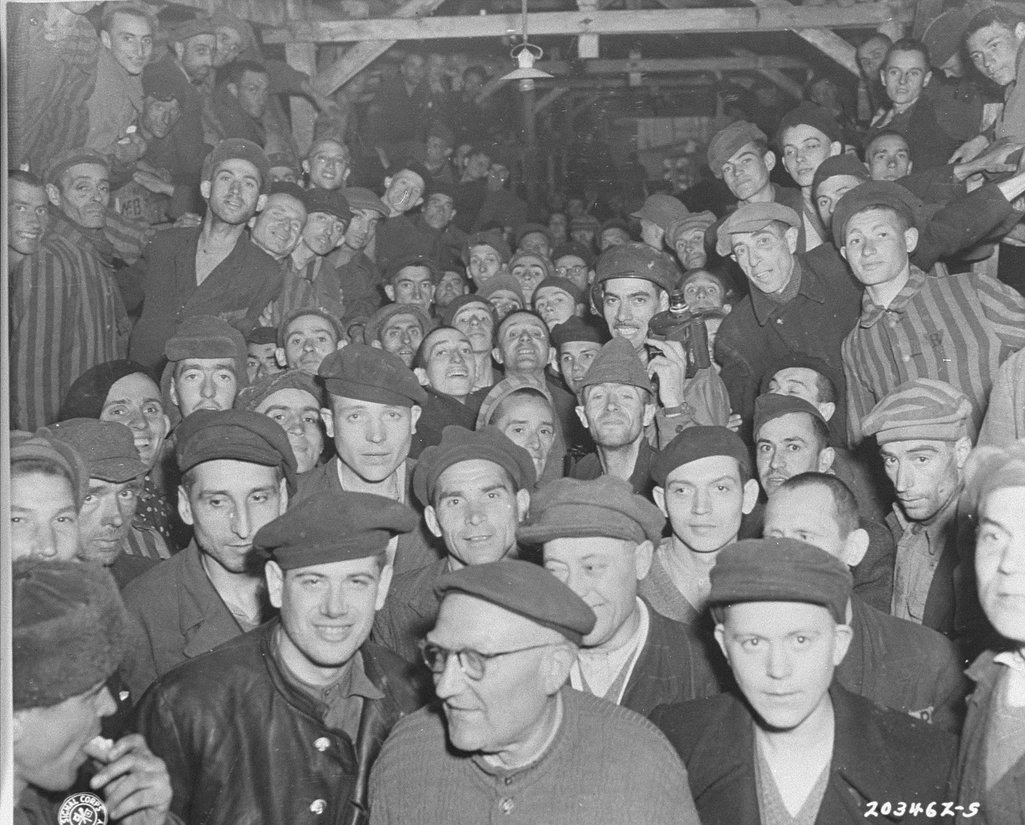 "Newly liberated inmates crowd into a barracks in Buchenwald.    Original caption reads, ""Photograph of a barracks in the German prison camp at Weimar, Germany, shows the crowded living conditions of the prisoners.  The building, which would normally house 50 people, was occupied by about 350.  The camp was taken by troops of the U.S. Third Army."""