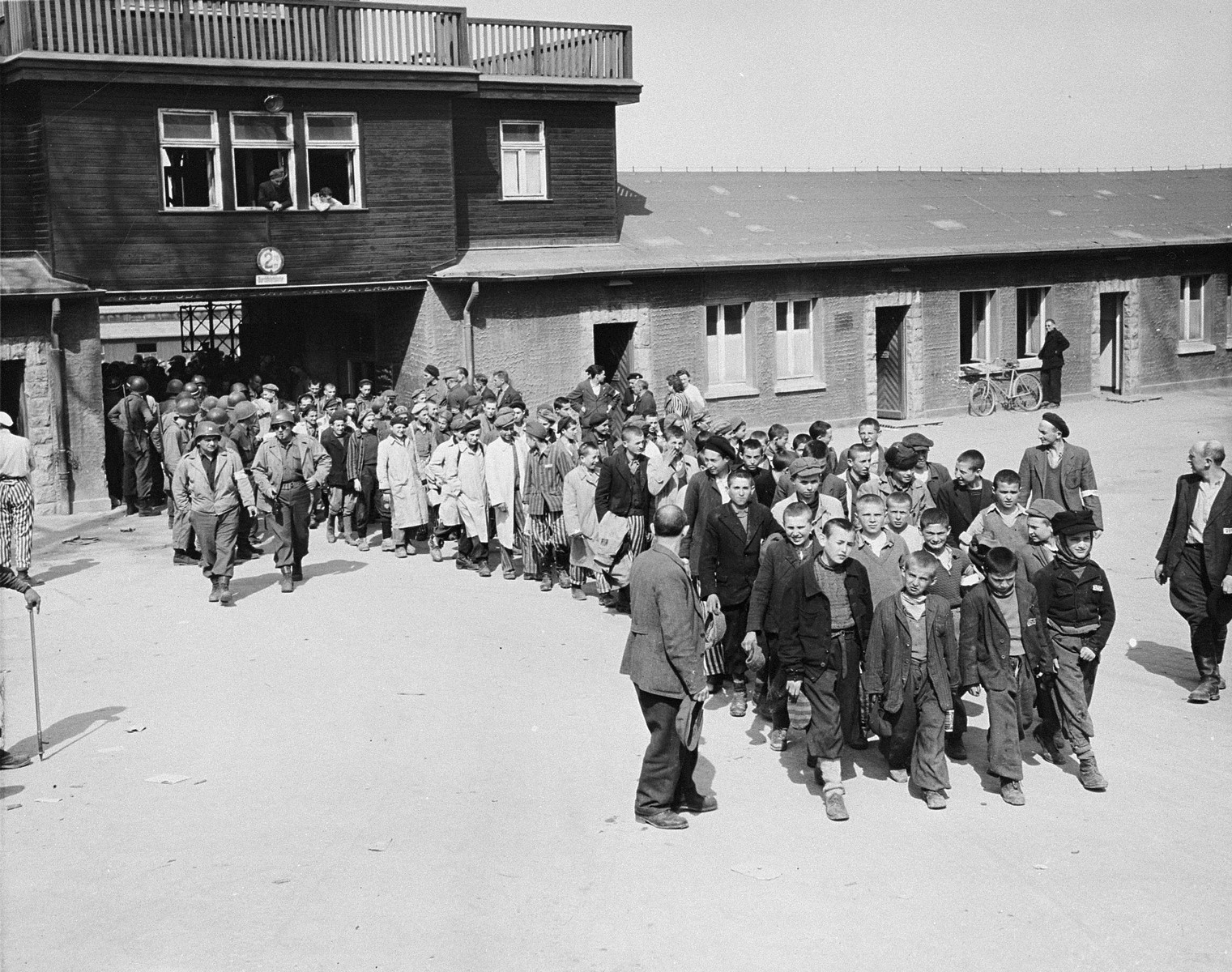"""Escorted by American soldiers, a transport of child survivors of Buchenwald file out of the main gate of the camp.  The original caption reads, """"Internees at the Buchenwald Concentration Camp near Weimar Germany march from the camp to receive treatment at an American hospital after the camp was captured by U.S. Third Army troops.""""  The boys are accompanied by American soldiers and directed by elements of the camp underground who watd over them, including Polish Jews Yakov Werber and Eli Grinbaum (on the right).   Among the children pictured are Izio Rosenman (head of column), Jacques Finkel, Charles Finkel, Fredek Margolis, Lalek Russ, Salek Sandowski, George Goldbloom and ? Zylber.  Misho Frailich, Willi Fogel, A. Grossman, Lotci Miller, Laiza Grynberg, Usha Grynberg, David Perlmutter, Marek Lodzinsky, Yankel Kapelush, Yosel Dziubak, Loyosh Hershkovitz, ? Yakubovitz, Reuven Wekselman, Stanley Weinstein, Herschek Zeit, Henryk Kolber, Jacques Werber and Philip Kaner.  Mor Stern is the boy in the beret and white coat, with right arm hanging down straight just right of the two American soldiers."""