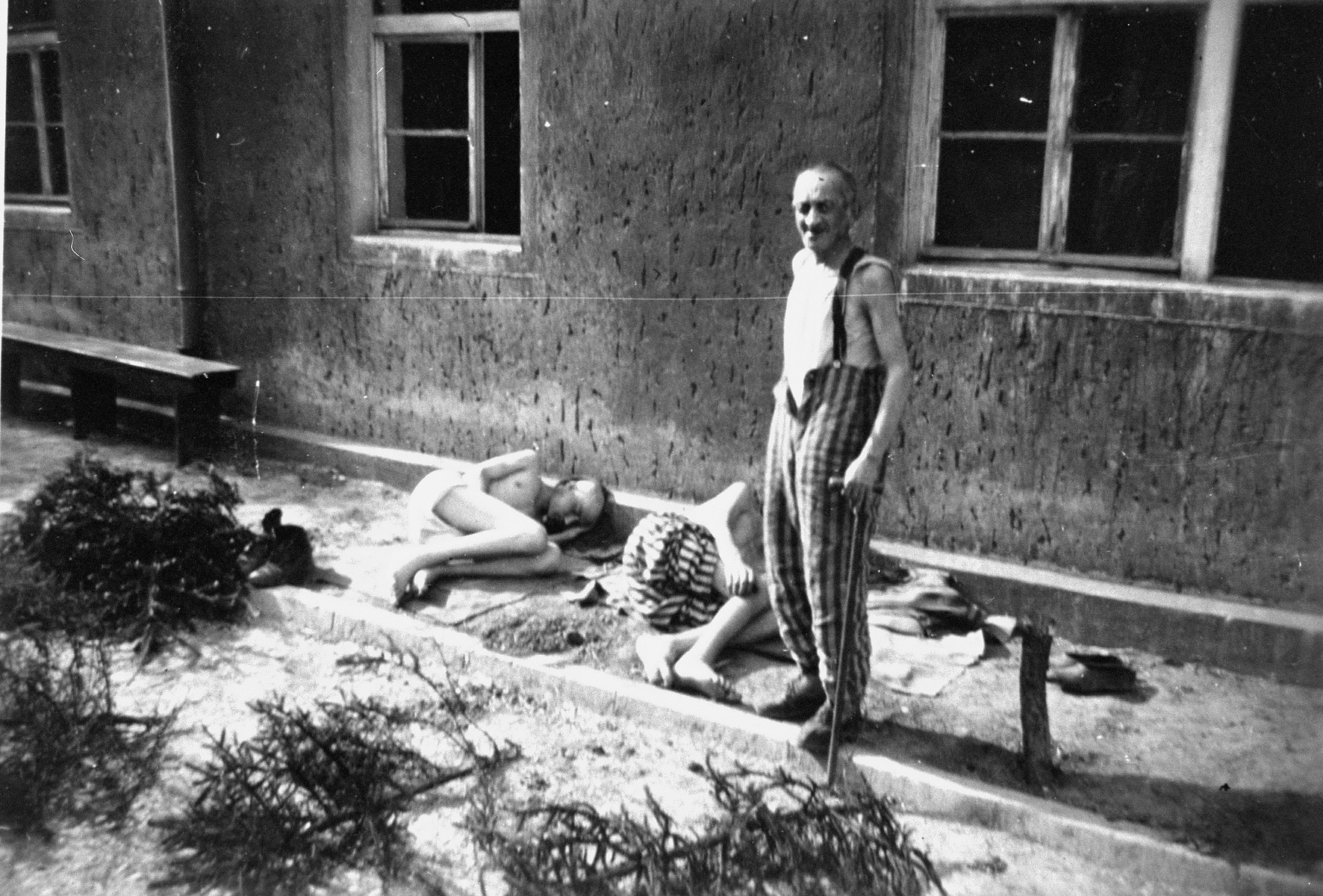 "Survivors in Buchenwald after liberation.  The two men on the ground are suffering from starvation.  The inscription on the back of the photograph reads, ""Typical prisoners Buchenwald Prison Camp.  5/7/45.  Two laying down, were to [sic] weak to say 'thank you,' just nodded their heads about an inch."""