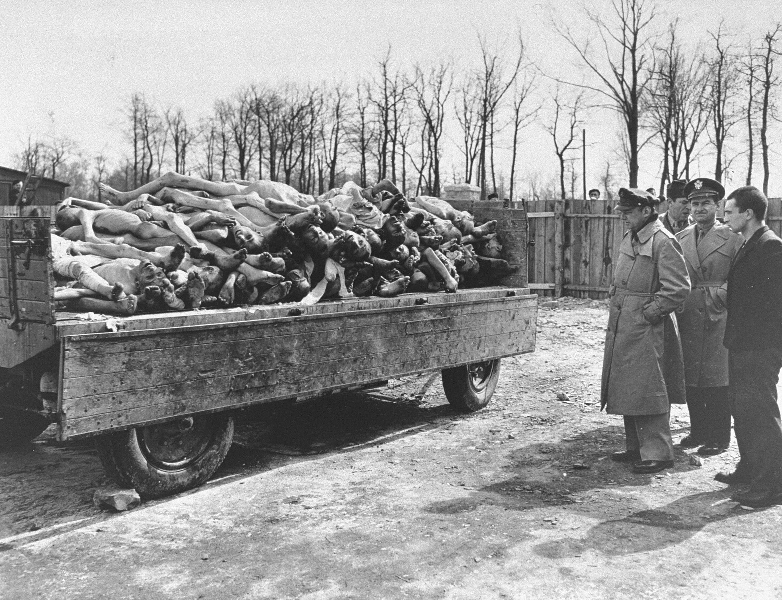 Three American radio journalists view a wagon full of corpses during a tour of the liberated Buchenwald concentration camp.  Pictured from left to right are, Lowell Thomas (NBC); Howard Barnes (WOR); and George Hamilton Combs (WHN).