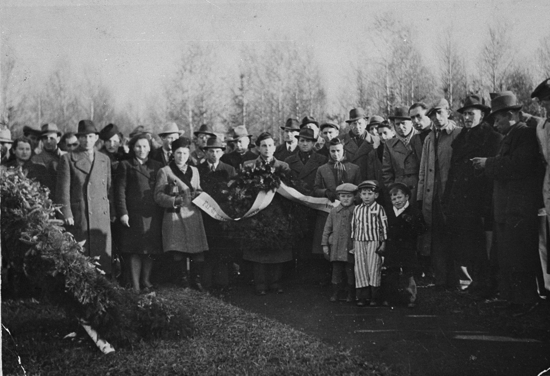 Jewish DPs attend a memorial service in the Buchenwald concentration camp.    The little boy in the concentration camp uniform may be Joseph Schleifstein.