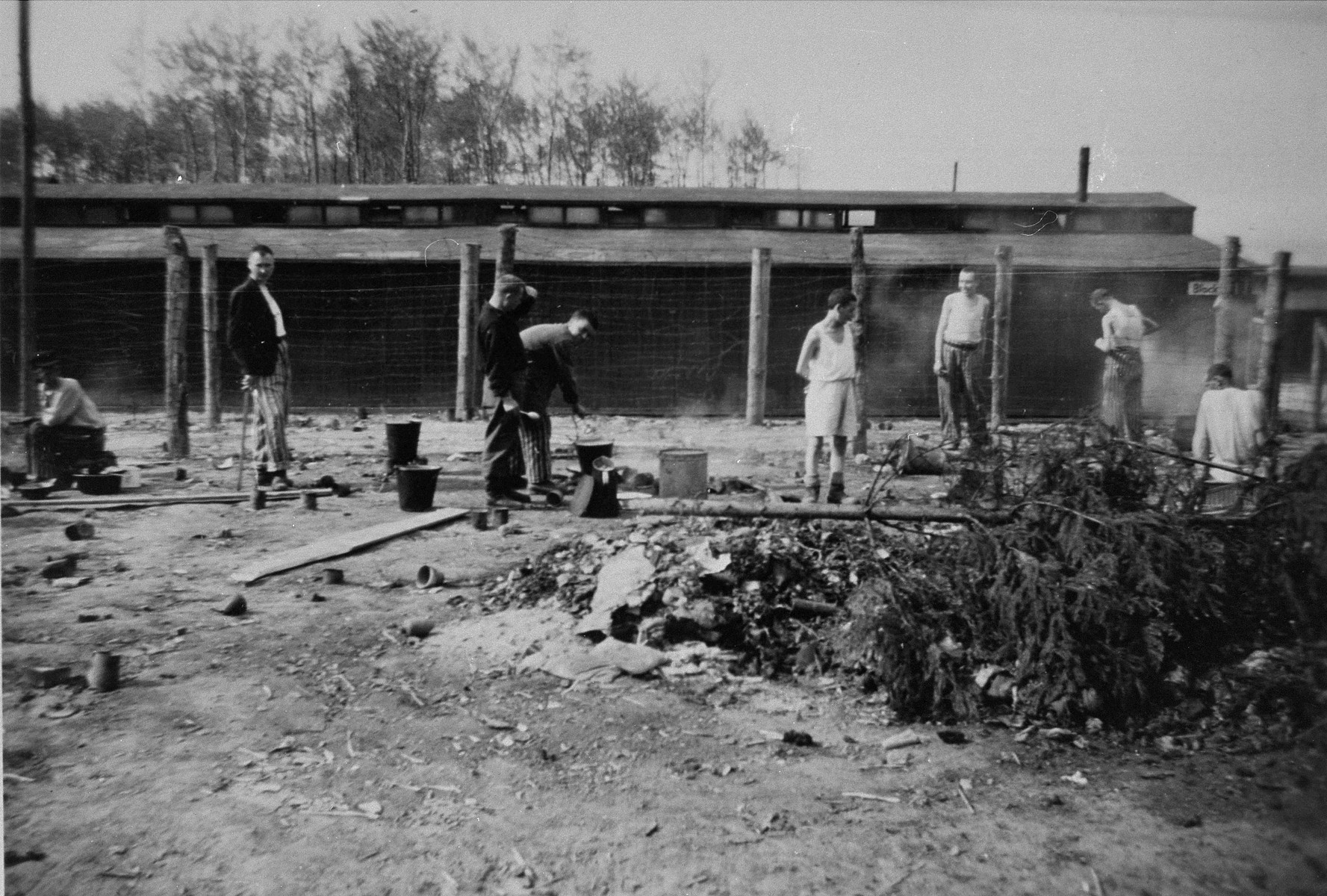 "Survivors in Buchenwald preparing their noon meal after liberation.  The inscription on the back of the photograph reads, ""Buchenwald prisoners preparing noon meal.  5/9/45."""