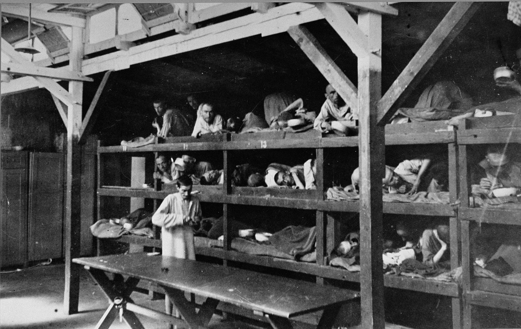 "Survivors lie in multi-tiered bunks in a barracks in the newly liberated Buchenwald concentration camp.  The original caption reads ""Here is a Nazi hospital ward in Buchenwald concentration camp.  The sick prisoners who were still able to move about cared for those in the cribs."""