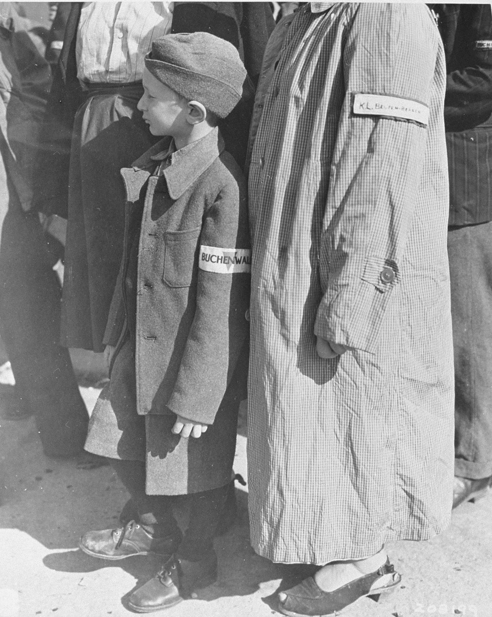 A six-year old survivor waits for his name to be called at a roll call in Buchenwald for departure to Switzerland, shortly after the liberation of the concentration camp.    Pictured is Stefan Jakubowitz.  His parents and two brothers all survived.  A United Nations Relief and Rehabilitation Administration worker is calling off names of children in the group of 350 orphans scheduled for departure to Switzerland.  The children, who range in age from five to eighteen years, are all orphans of the war and some of them have been at the camp for as long as six years.  They are Polish, Russian, Yugoslavian, and Czech.