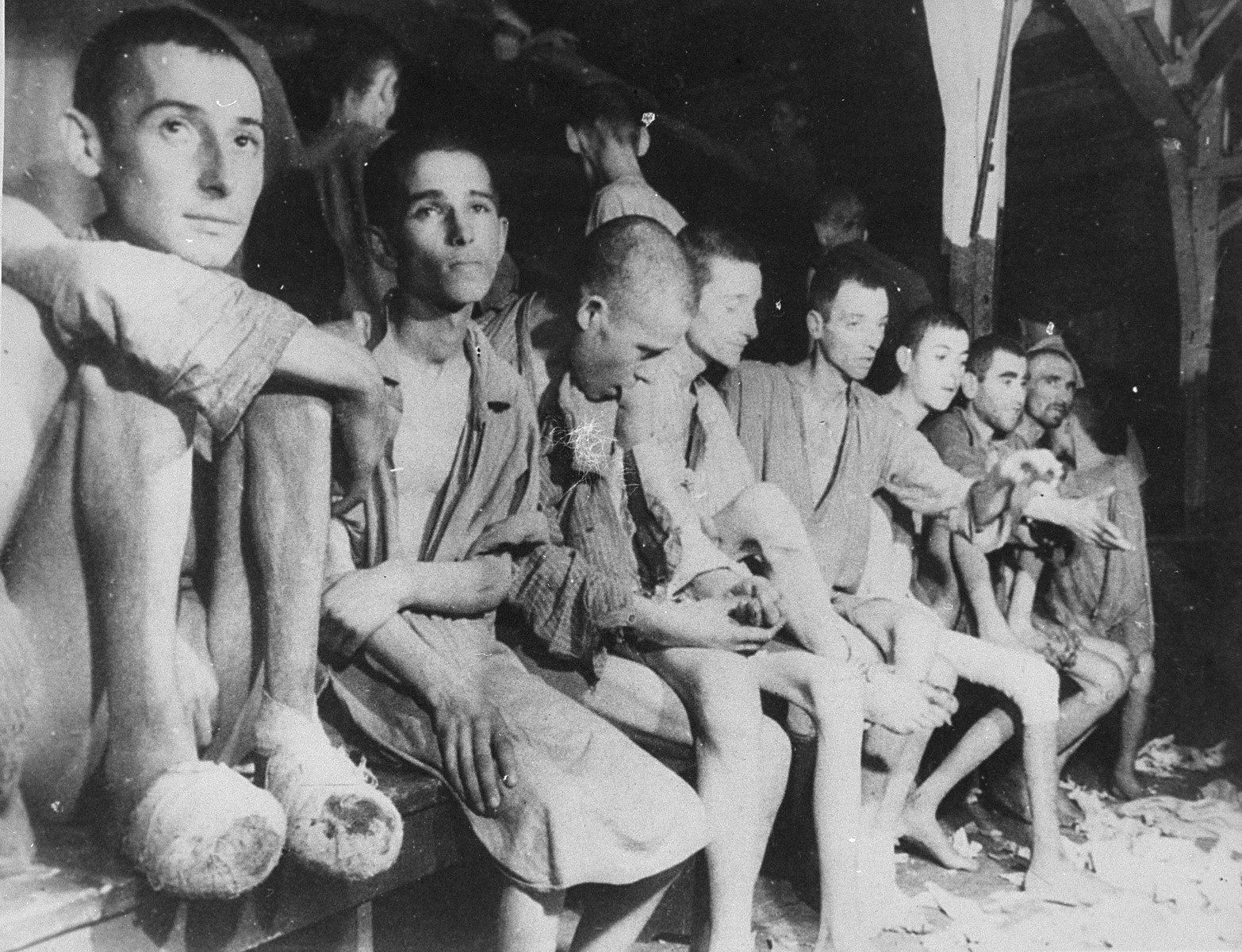 "Wounded and sick survivors, Russians, Poles, and Jews, sitting on a bench inside a barracks in Buchenwald concentration camp.  The original caption reads, ""A benchful of diseased prisoners, largely Russian, some Polish.  Here are many Jews in these barracks, some can be seen in the tiers of the beds which are behind the hospital group."""