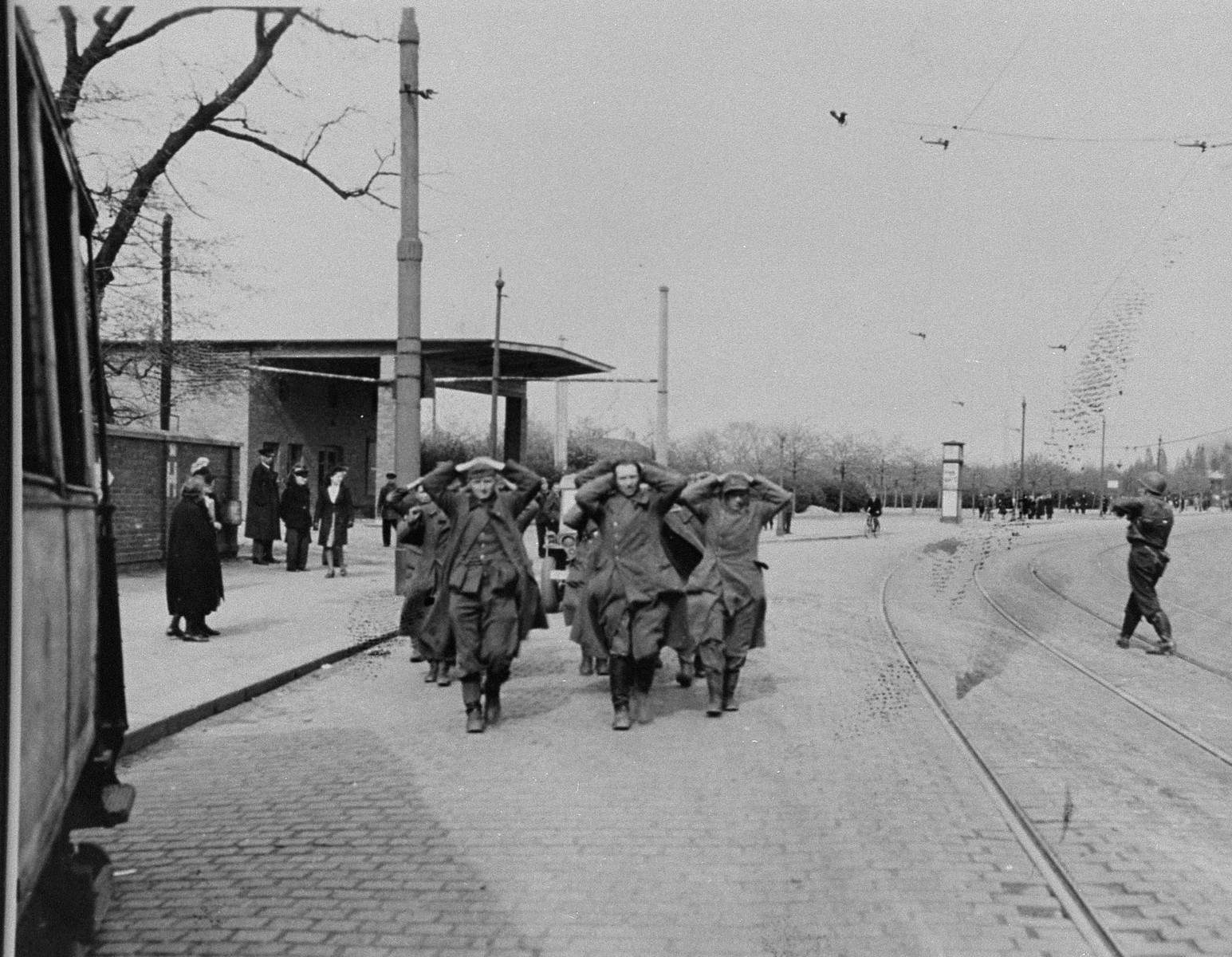 Former SS guards from Buchenwald who have been captured by American troops, march along a street with their hands behind their heads.