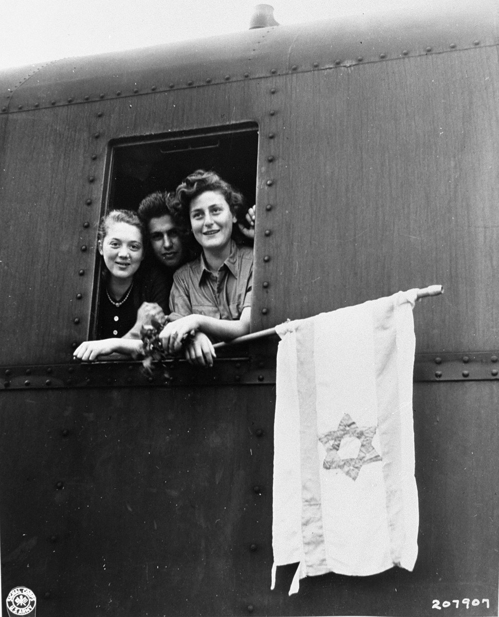 "Three young Jewish DPs look out of the window of their train holding a homemade Zionist flag as they depart from Buchenwald on the first leg of their journey to Palestine.   The original caption reads, ""These three Jewish children are on their way to Palestine after having been released from the Buchenwald concentration camp.  The girl on the left is from Poland, the boy in the center is from Latvia and the girl on the right is from Hungary.""  Pictured are: Yetti (Yocheved) Halpern Beigel (left); Martha Weber (right); and an unidentified Jewish youth from Latvia."