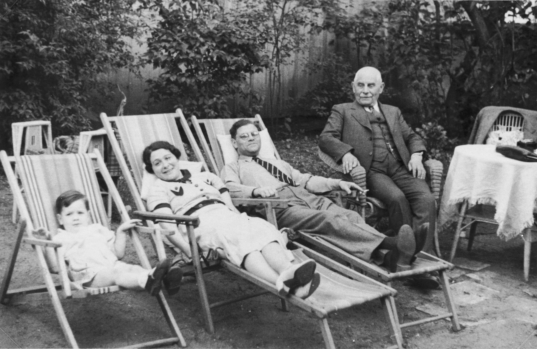 The Jacobsohn family relaxes outside on lawn chairs.  Pictured from left to right are: Rudolf, Margaret and Erich Jacobsohn and Erich's father, George Jacobsohn.