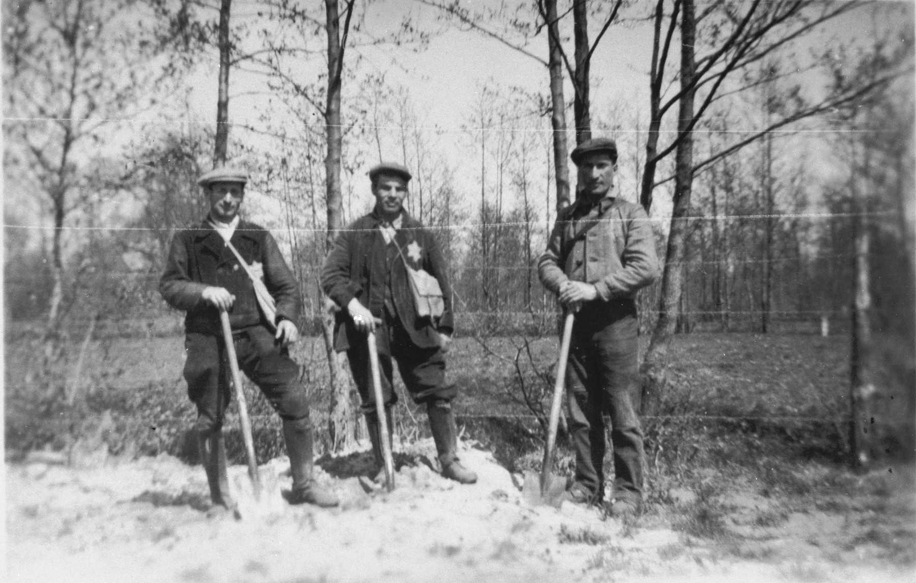 Prisoners wearing Jewish stars from the Staphorst-Rouveen labor camp remodel graves for a Christian church.  Pictured from left to right are M. Cohen, L. Waterman and Coenraad Rood.