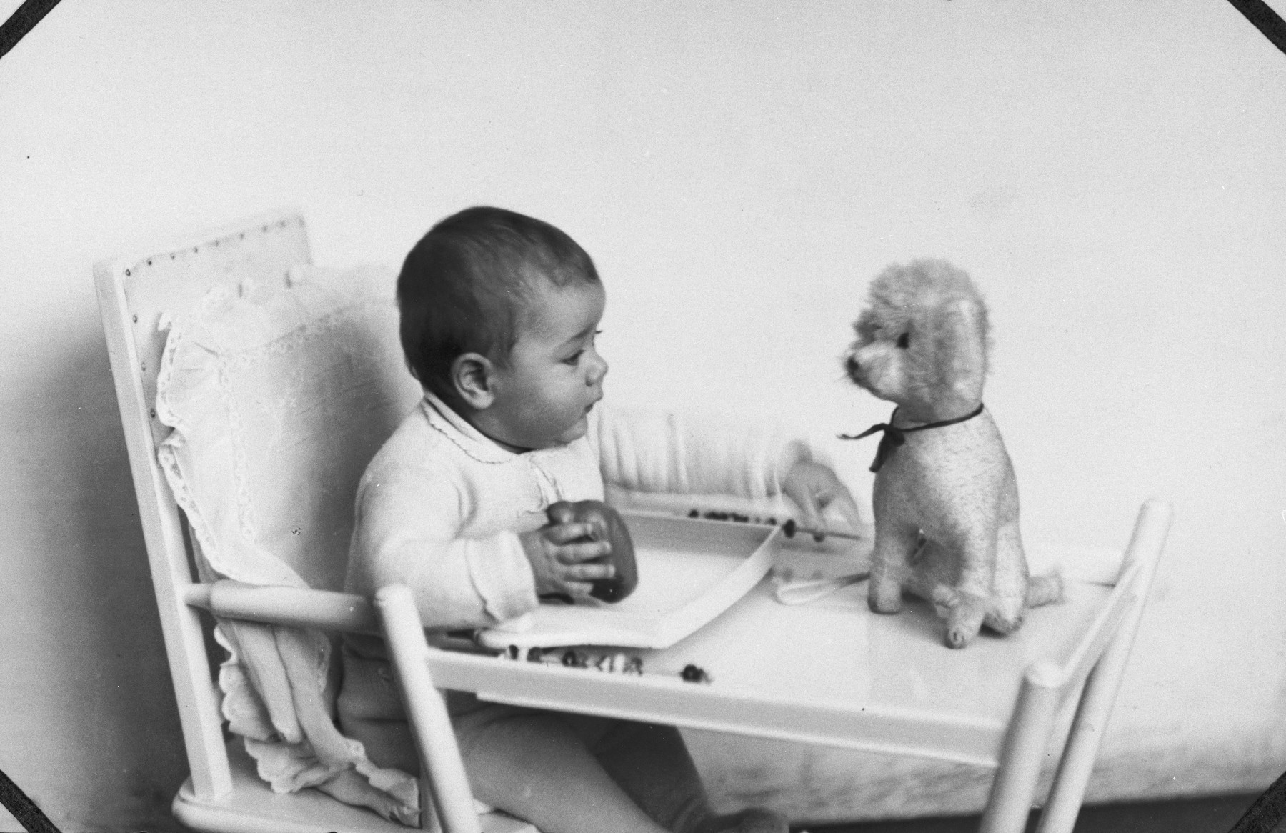 Portrait of Rudolf Cohen as an infant seated in a high chair with a stuffed dog.