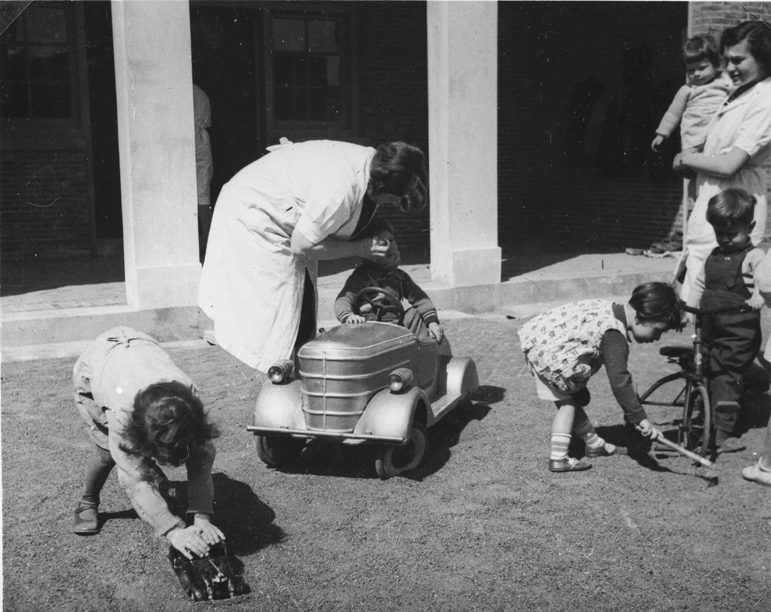Childcare workers at the creche for Jewish refugee children sponsored by the International Committee for European Immigrants in Shanghai, assist preschoolers who are playing in the courtyard.  One photograph from a second International Committee album prepared for I.C. secretary Paul Komor.