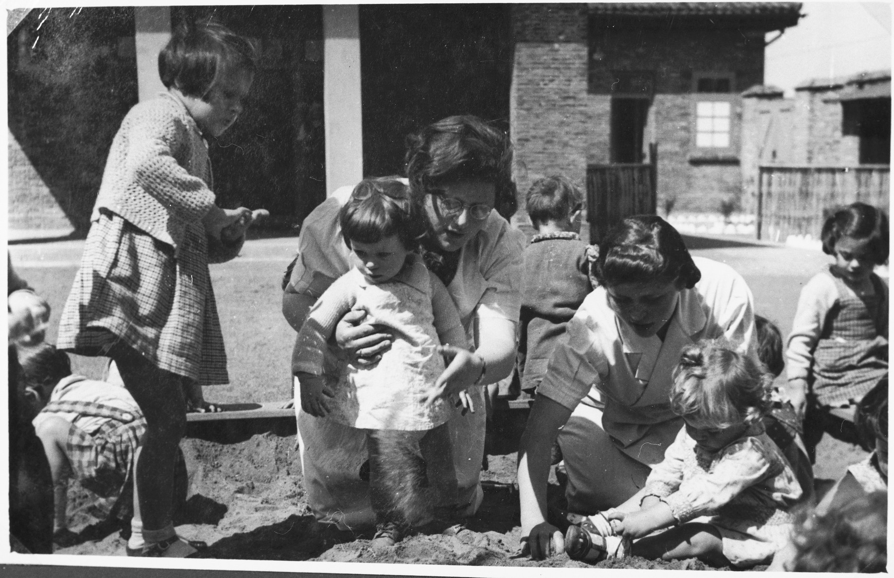 Childcare workers at the creche for Jewish refugee children sponsored by the International Committee for European Immigrants in Shanghai, play in the sand with a group of preschoolers.  One photograph from a second International Committee album prepared for I.C. secretary Paul Komor.