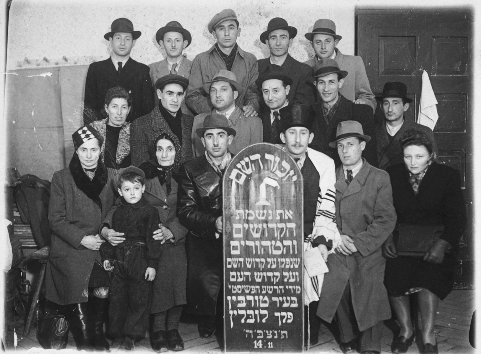 Jewish survivors from Turobin pose with a memorial plaque commemorating the victims of Nazism from their community.  Cantor Iber is pictured in the tallit.  Trained in the Vilna Conservatory, he served as the cantor in the Ulm DP camp.