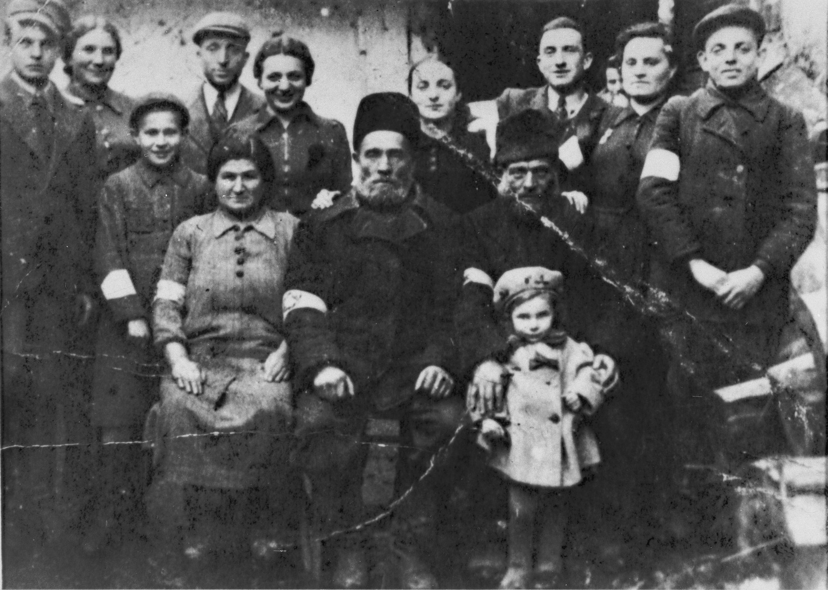 Portrait of the extended Lachter family wearing armbands in the Turobin ghetto.  Standing in front is the child Devorah Lachter.  Seated from left to right are: Chaja and Mottel Leichter, with Mottel's brother Moshe Lachter.  Standing behind them from left to right are: Ozer Leichter, Chaya Golda Lachter, Shaya Leichter, Avrumcha Lachter, Chuma Lachter, Miriam Lachter, Moshe-Leib, Sura Leichter, and Ozer Lachter.  This photograph was sent to Yosef Lachter and his cousin Herish Leichter who had fled to the Soviet zone at the start of the war.  Fearing they would never see their family again, the cousins requested that a family portrait be sent to them.  Thinking that as religious Jews, their family would be reluctant to have themselves photographed, the cousins wrote that they needed the complete family portrait for official identification.