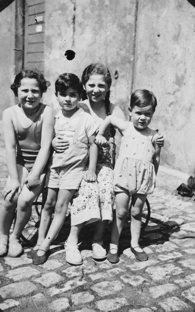 Four children pose outside on a summer day.  Pictured is Rudolf Cohen Jacobsohn (right) with his cousins Inge and Howard Spicker and a neighbor.