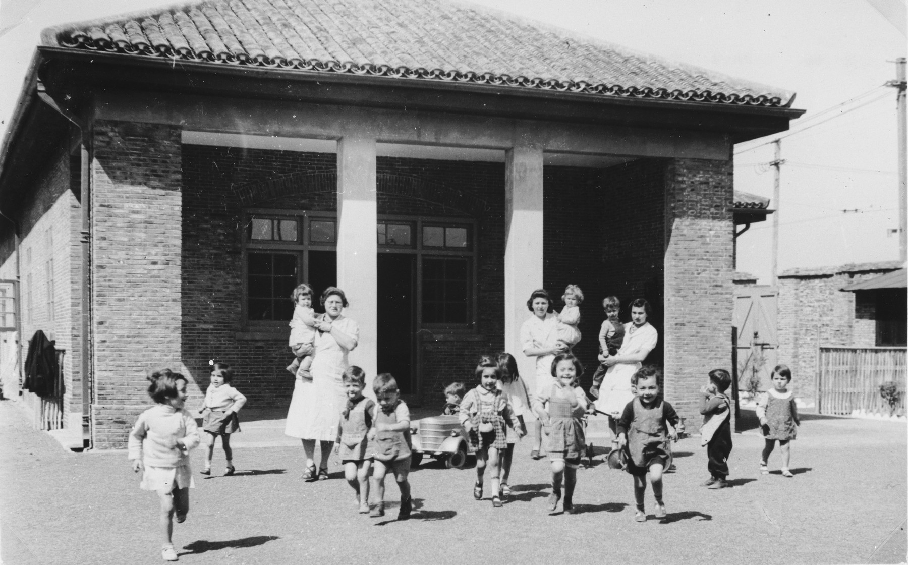 """Children and staff of the International Committee creche for Jewish refugees in Shanghai.  One photograph from the International Committee album, """"Introducing the I.C. Staff"""" presented to I.C. secretary Paul Komor on August 7, 1941 in Shanghai."""