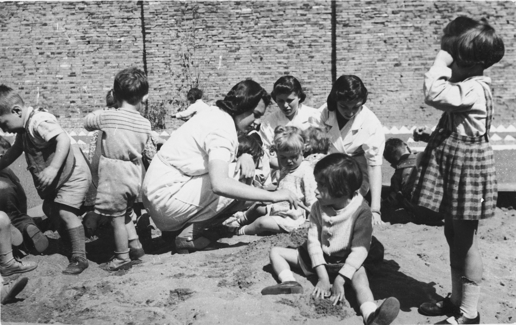 Childcare workers at the creche for Jewish refugee children sponsored by the International Committee for European Immigrants in Shanghai, assist preschoolers who are playing in the sand.  One photograph from a second International Committee album prepared for I.C. secretary Paul Komor.