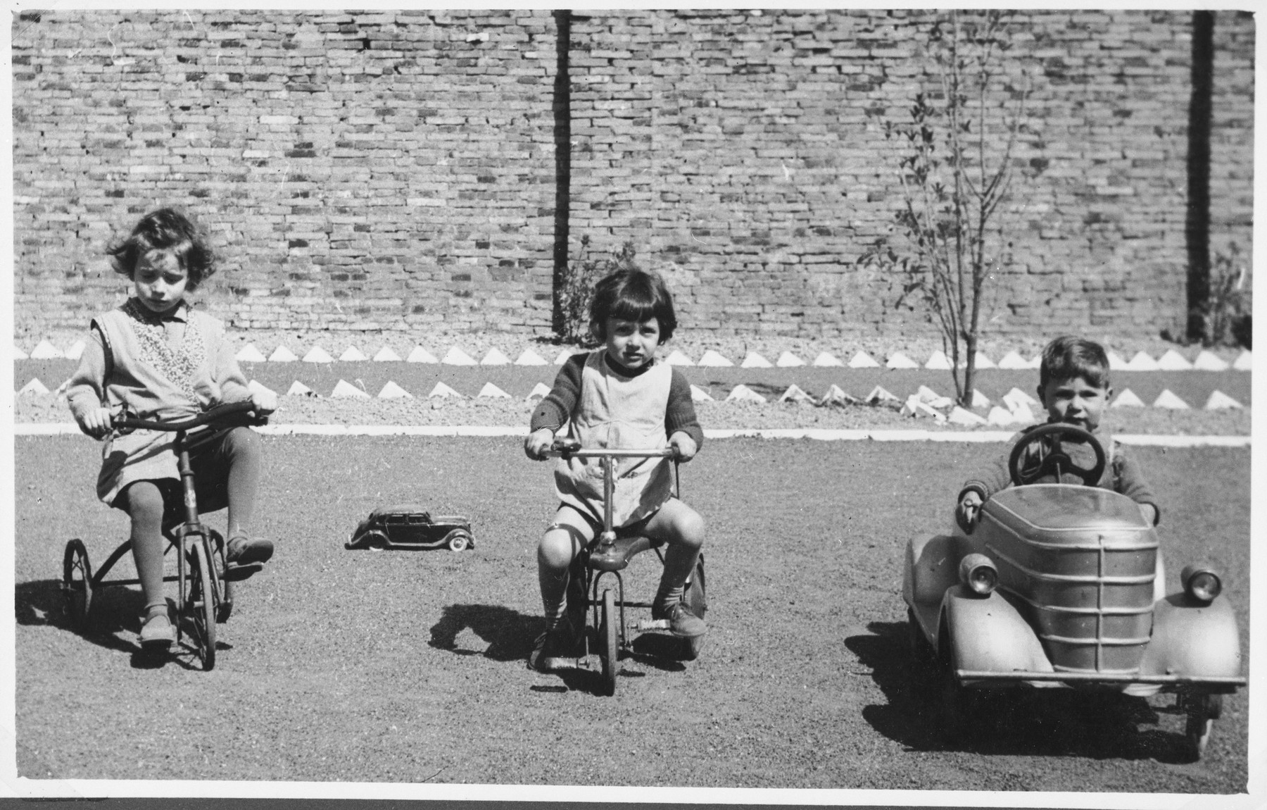 Three refugee children at the creche for Jewish refugee children sponsored by the International Committee for European Immigrants in Shanghai, ride tricycles and toy cars in the courtyard.  One photograph from a second International Committee album prepared for I.C. secretary Paul Komor.