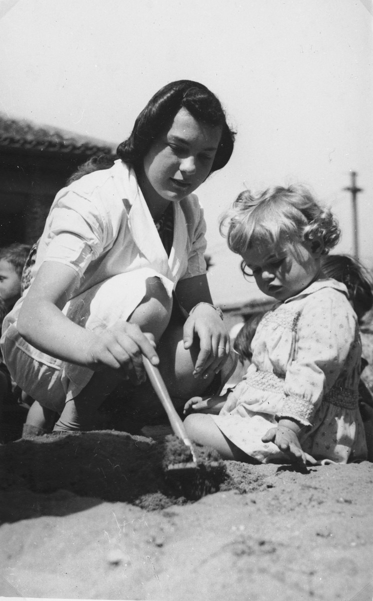 A childcare worker at the creche for Jewish refugee children sponsored by the International Committee for European Immigrants in Shanghai, play in the sand with a group of preschoolers.  One photograph from a second International Committee album prepared for I.C. secretary Paul Komor.
