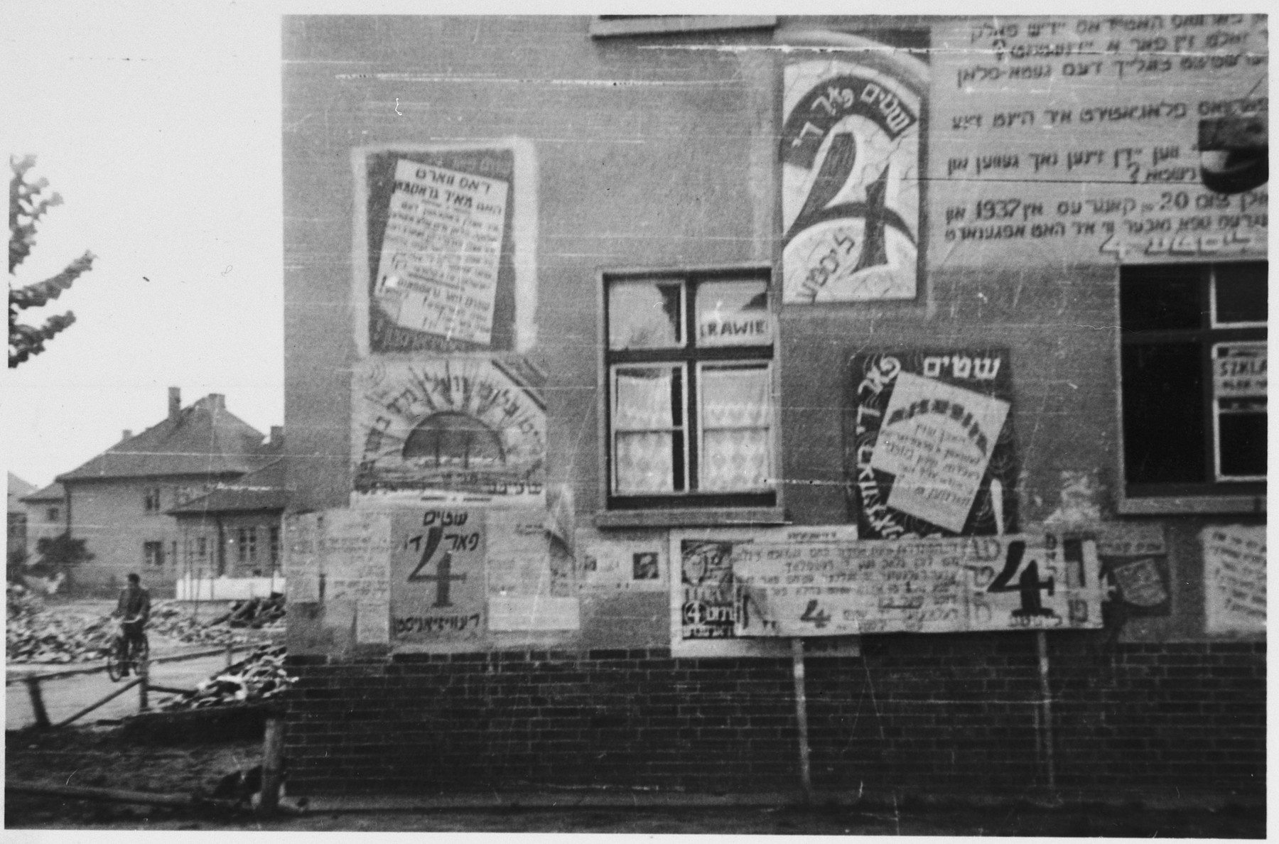 Assorted election signs are posted on the outside wall of a barracks in the Bergen-Belsen displaced persons camp.