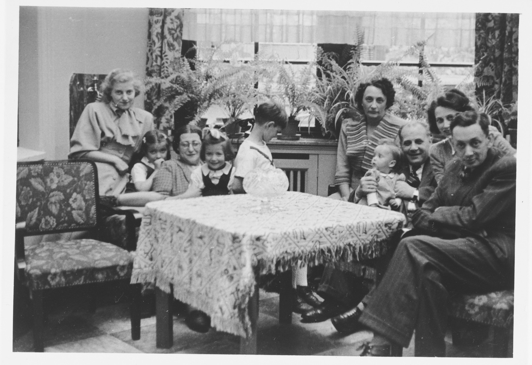 The Wollheim and Fabian families sit together in the living room of the home they shared following the imposition of the Berlin blockade.