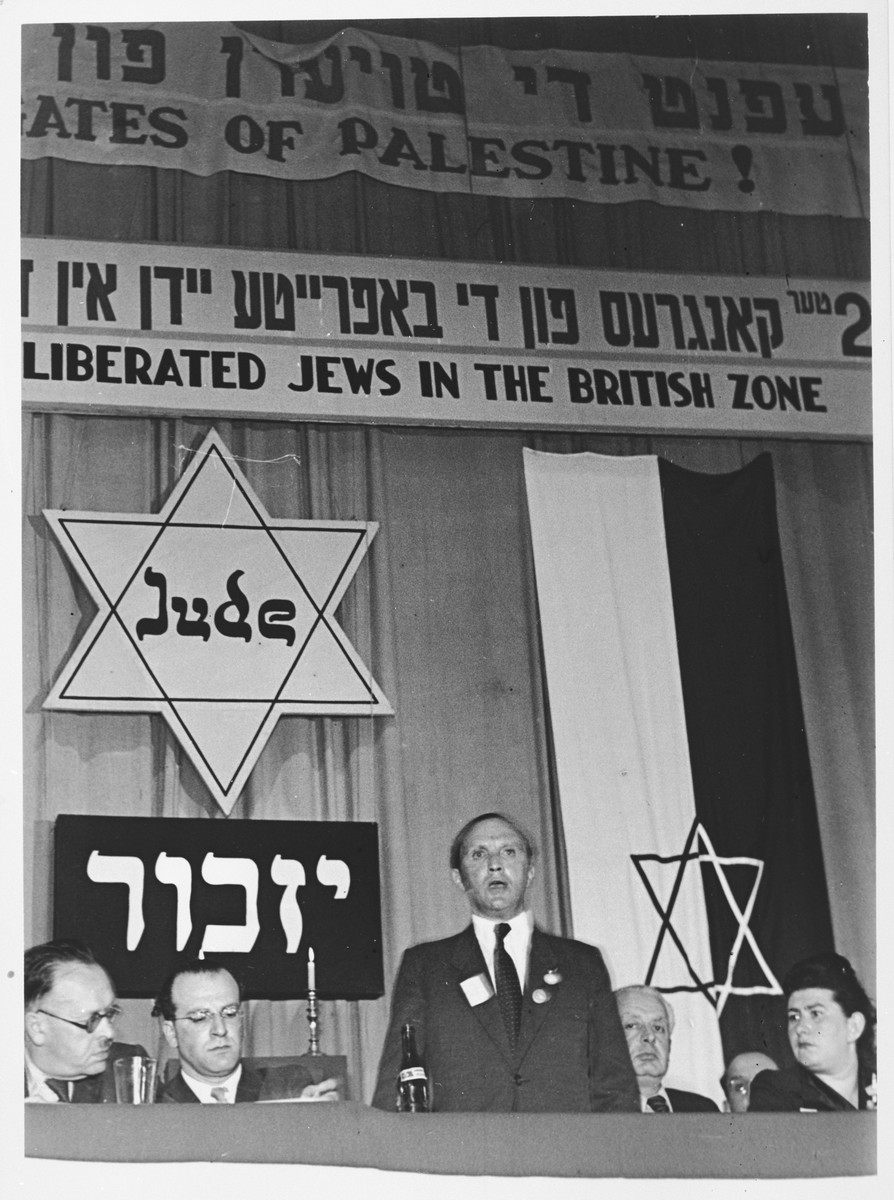 Josef Rosensaft addresses a session of the Second Congress of Liberated Jews in the British Zone at the Belsen displaced persons camp.  Also pictured are Norbert Wollheim (second from the left) and Hadassah Bimko (right).