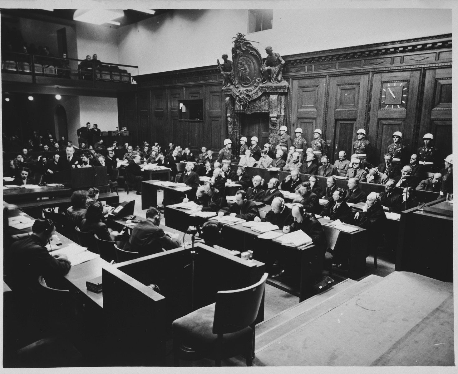View of the courtroom during a session of the International Military Tribunal trial of war criminals at Nuremberg.  In the foreground is the witness chair.  In the background at the left, Justice Robert Jackson delivers his opening address.
