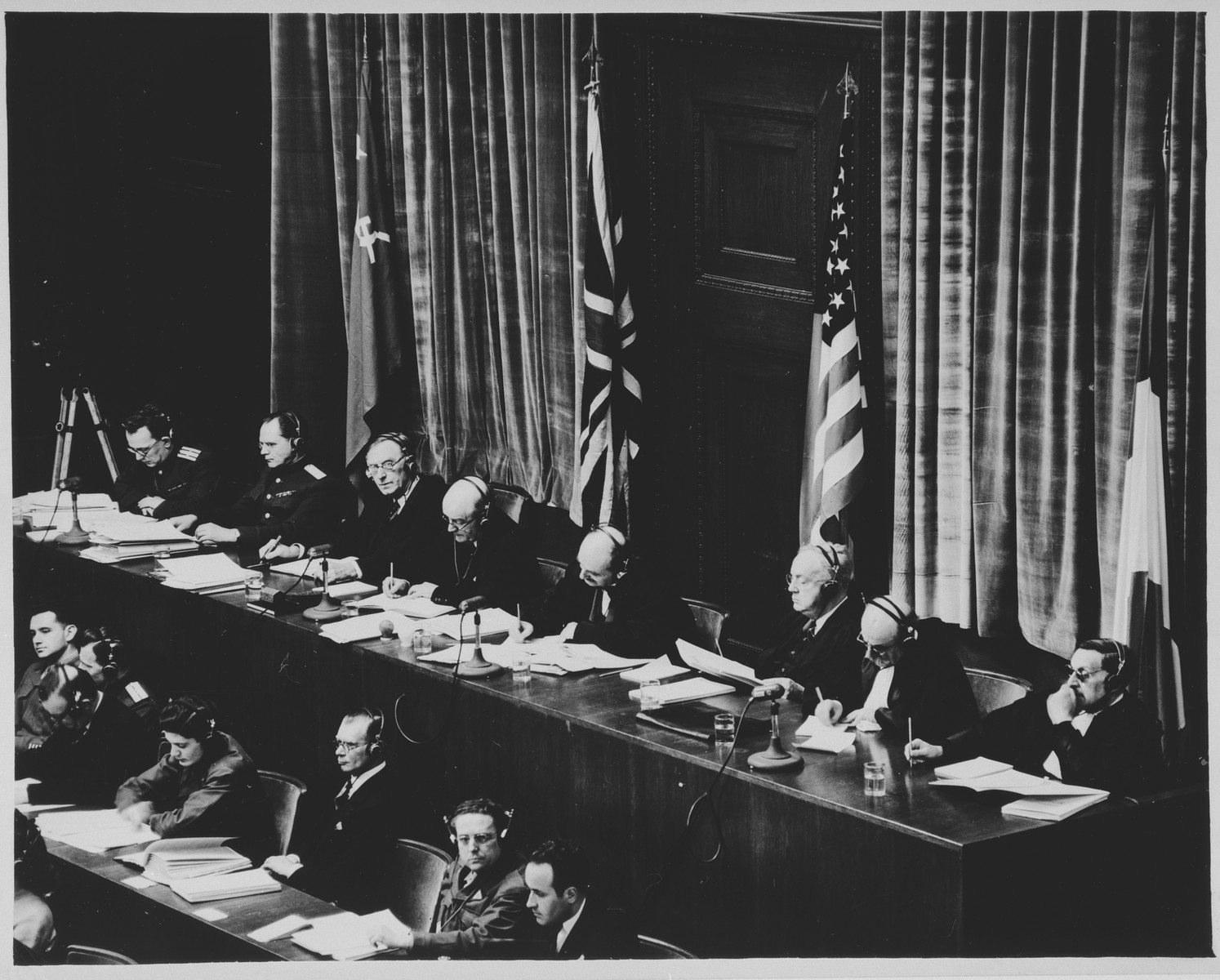 View of the tribunal during a session of the International Military Tribunal trial of war criminals at Nuremberg.  Pictured from left to right are: Alexander Federovich Volchkov, Alternate Soviet Judge; Major General Ion Timofeevich Nikitchenko, Sir Normann Birkett, British judge; Sir Geoffrey Lawrence, British judge; Francis Biddle, US judge; John J. Parker, Alternate US judge; Donnedieu de Varbes, French judge; Robert Falco, Alternate French judge.