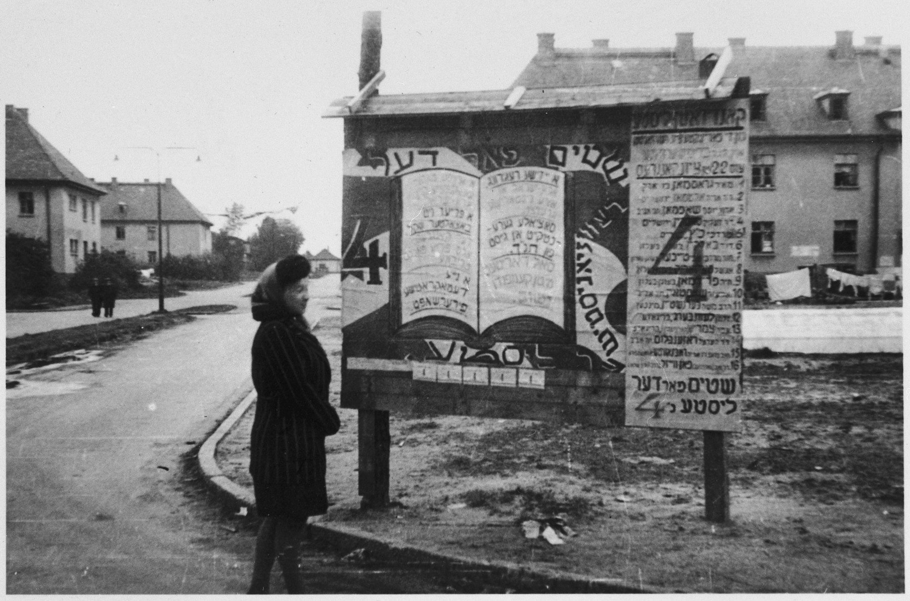 A woman reads election signs that are posted on a bulletin board in the Bergen-Belsen displaced camp.