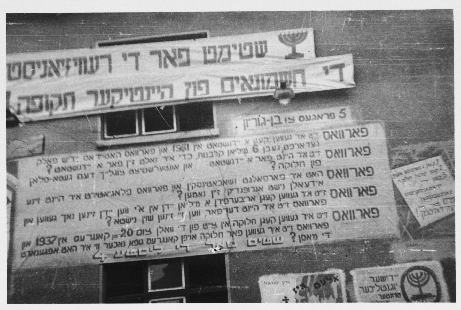 "Zionist election banners are posted on the exterior of a barracks in the Bergen Belsen displaced persons camp.  The banner at the top reads: ""Vote for the revisionists; the Hasmoneans of the current period.""  Beneath, is a banner listing five questions for David Ben-Gurion to answer."