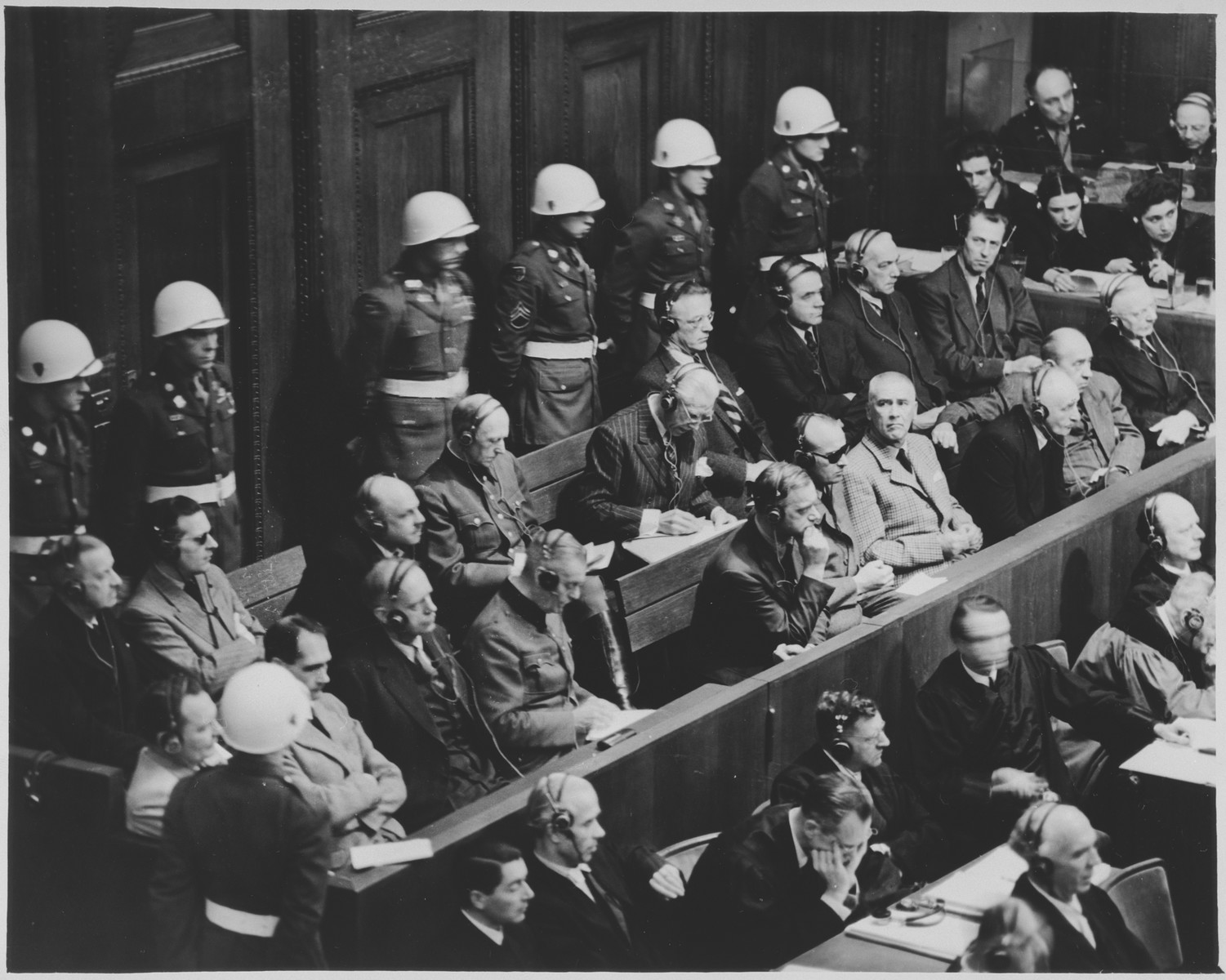 View of the defendants dock at the International Military Tribunal trial of war criminals at Nuremberg.  Seated in front of the defendants are the translators.  Mr. Walter Seligson, translation supervisor (a German Jew owho immigrated first to Palestine and then to the United States) is seated fourth from the left.