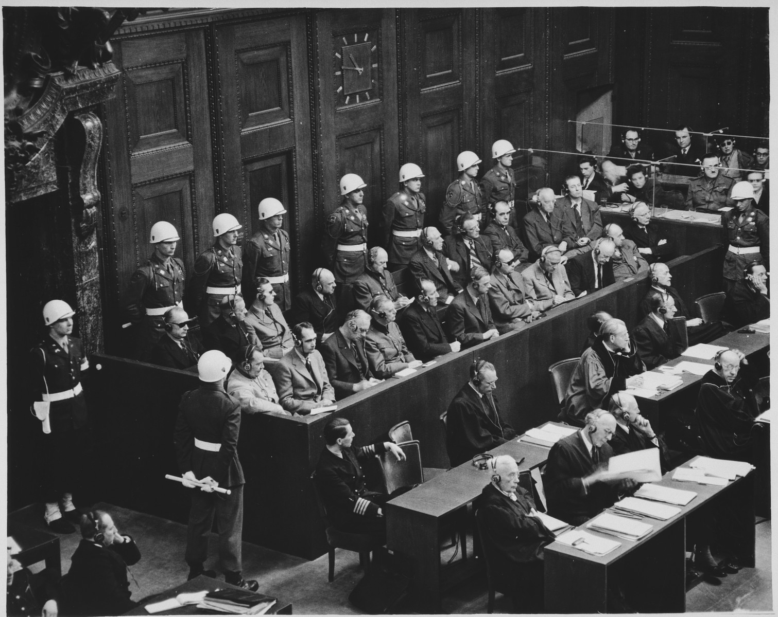 View of the defendants dock at the International Military Tribunal trial of war criminals at Nuremberg.  Pictured in the front row from left to right are: Goering, Hess, Ribbentrop, Keitel, Kaltenburnner, Rosenberg, Frank, Frick, Streicher, Funk and Schacht.  In the second row are Doenitz, Raeder, Schirach, Saukel, Jodl, Papen, Seyss-Inquart, Speer, von Neurath and Fritsche.  Sitting in front of them are their defense counsel.  The naval officer sitting among the lawyers is Dr. Otto Kranzbuehler, the defense counsel for Karl Doenitz, who was given a temporary release from the POW camp when Doenitz requested him to be his lawyer.  At the bottom left corner is General R. A. Rudenko, the chief Soviet prosecutor.