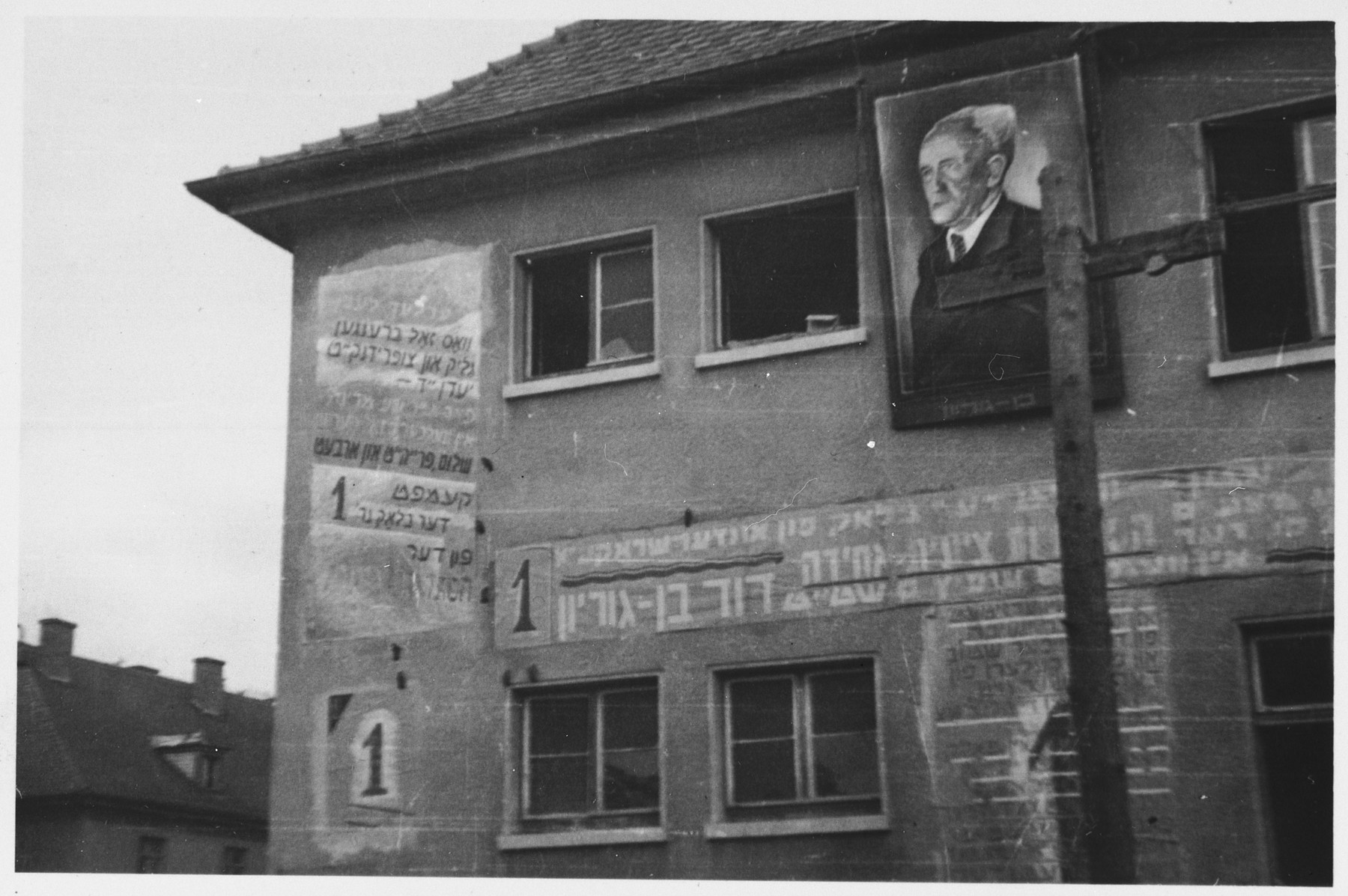 Assorted election posters and a portrait of David Ben-Gurion are posted on the outside wall of a barracks in the Bergen-Belsen displaced persons camp.