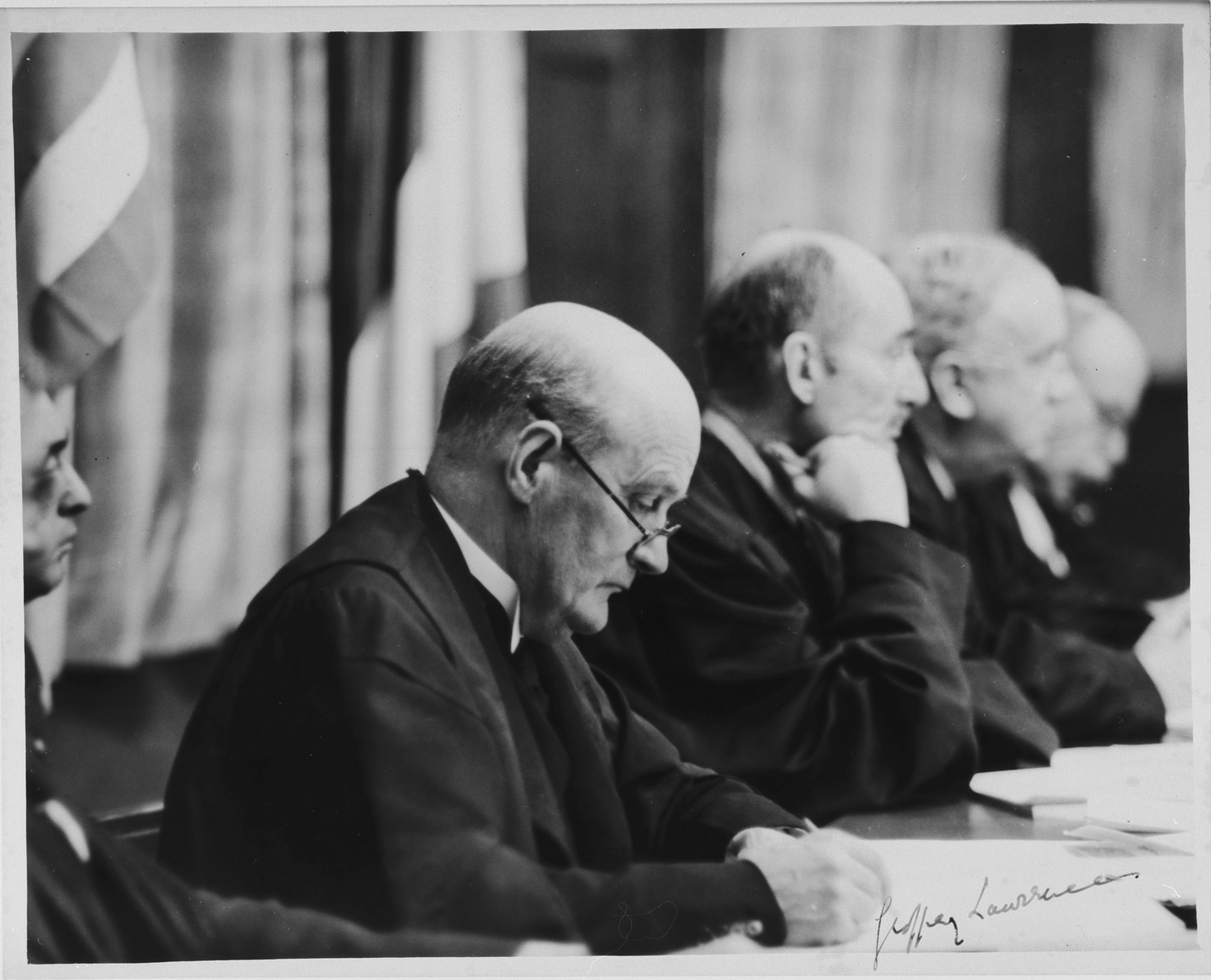 Presiding judge, Sir Geoffrey Lawrence, KC, sits on the bench during a session of the International Military Tribunal trial of war criminals at Nuremberg.  Visible in the background are Judge Francis Biddle, Justice John L. Parker and Justice Donnedieu de Varbes.