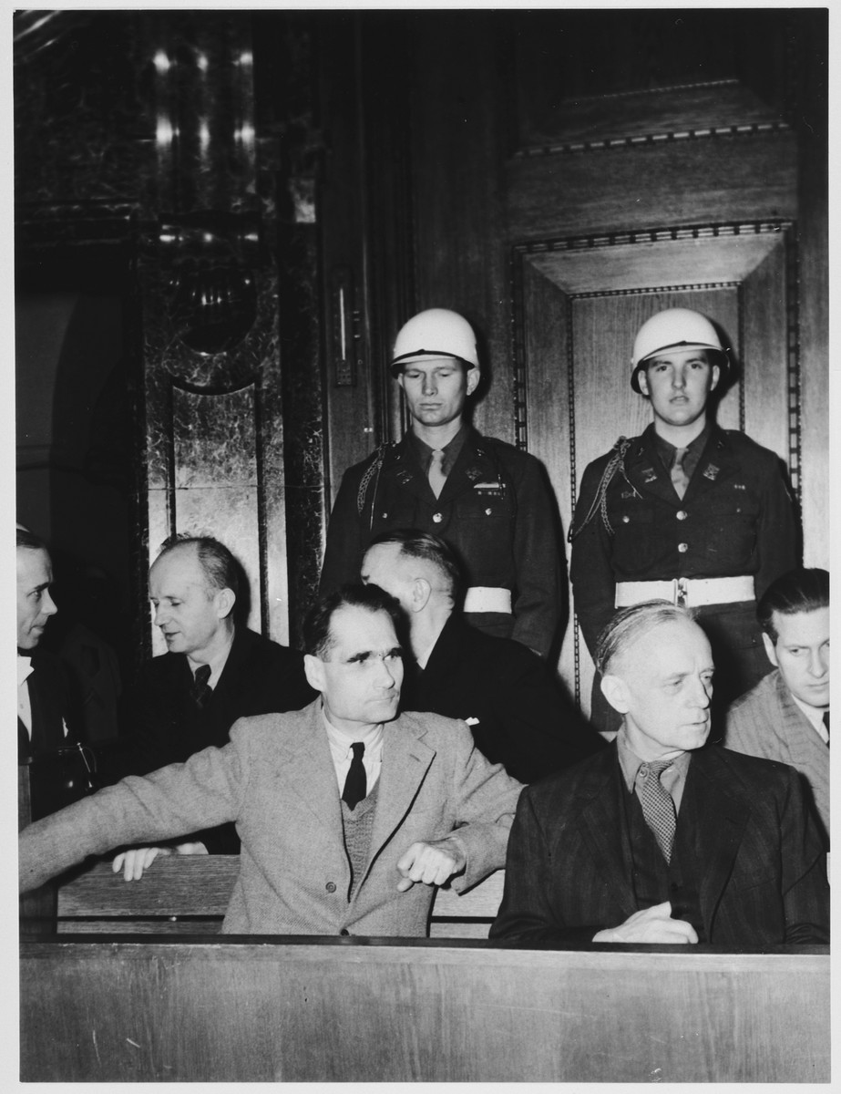 Defendants in the dock at the International Military Tribunal trial of war criminals at Nuremberg.    Pictured in the front are Rudolf Hess (left) and Joachim von Ribbentrop (right).  In the back row, left to right, are: Karl Doenitz, Erich Raeder, and Baldur von Schirach.