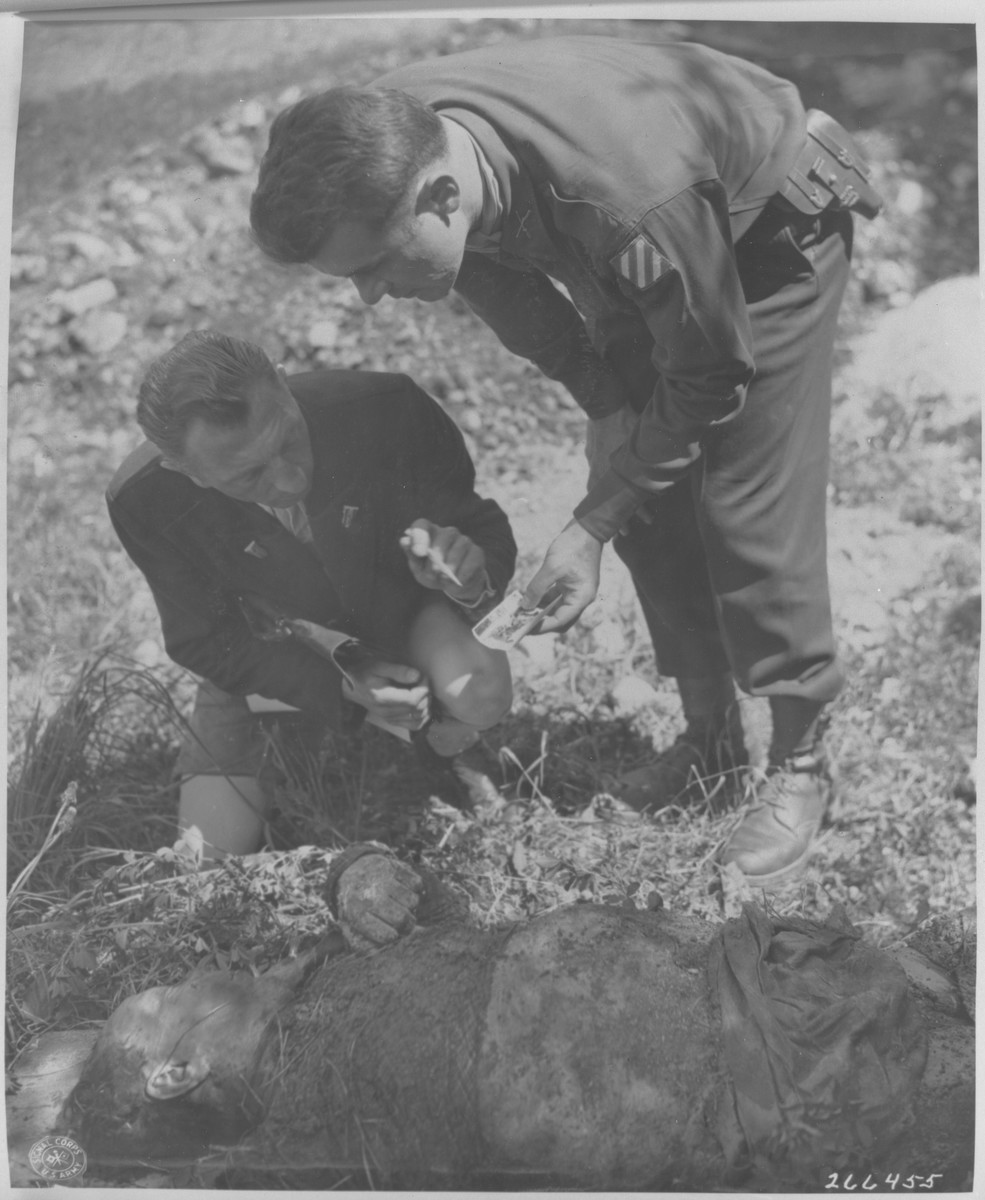 "Two war crimes investigators make a positive identification of the body of Robert Moser, which was exhumed from a mass grave by the war crimes branch for decent reburial.  Moser was beaten to death by the Gestapo on April 25, 1945.    Pictured are First Lieutenant Bert Engel (right), Commander of the War Crimes Branch of the U.S. Seventh Army, and Franz Ringer (left), chief civilian investigator for the War Crimes Commission in Innsbruck.  Ringer, formerly of Austrian counterintelligence, was imprisoned in Dachau for two and a half years.  Original caption reads, ""1/LT Bert C. Engel (VI Corps Det. Commander of the War Crimes Branch) and Franz Ringer (formerly of the Austrian C.I.D. and a prisoner at Dachau for 2 1/2 years, now acting  as Chief Civilian Investigator for The War Crimes comm. in Innsbruck) make a positive identification from A photograph of the body of Robert Moser, who had been beaten to death by the Gestapo on or about the 25th of April, 1945."""