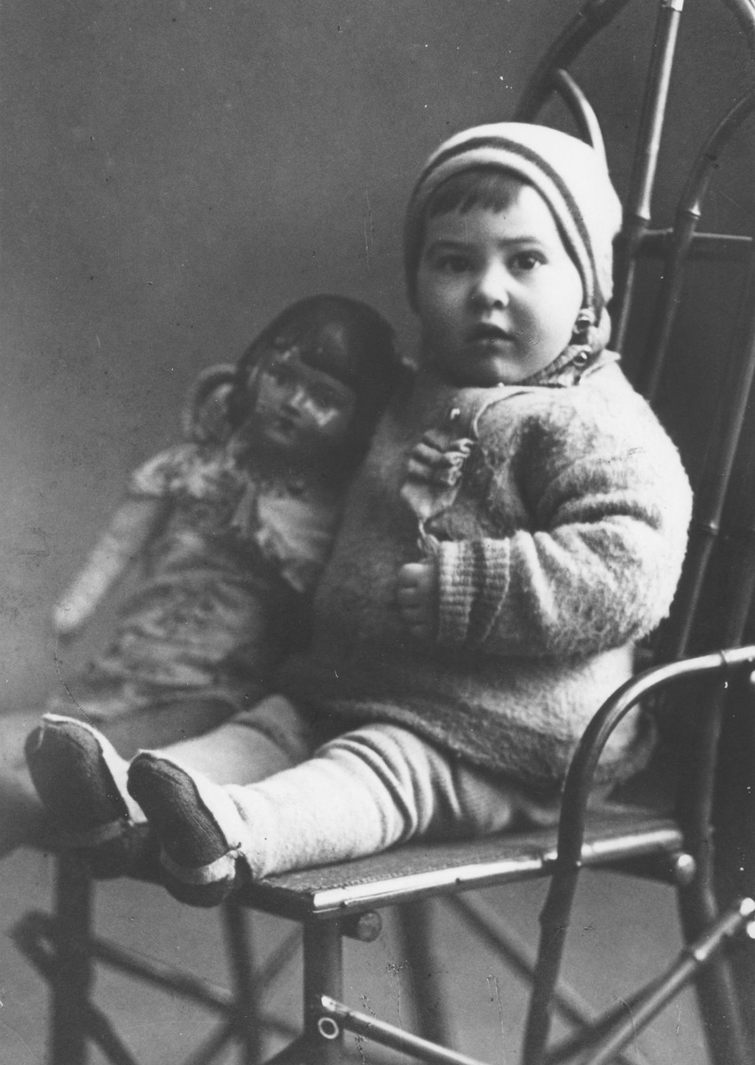 Studio portrait of a Jewish child posing on a chair with a doll in Sverdlovsk.  Pictured is two-year-old Cilia Jurer.