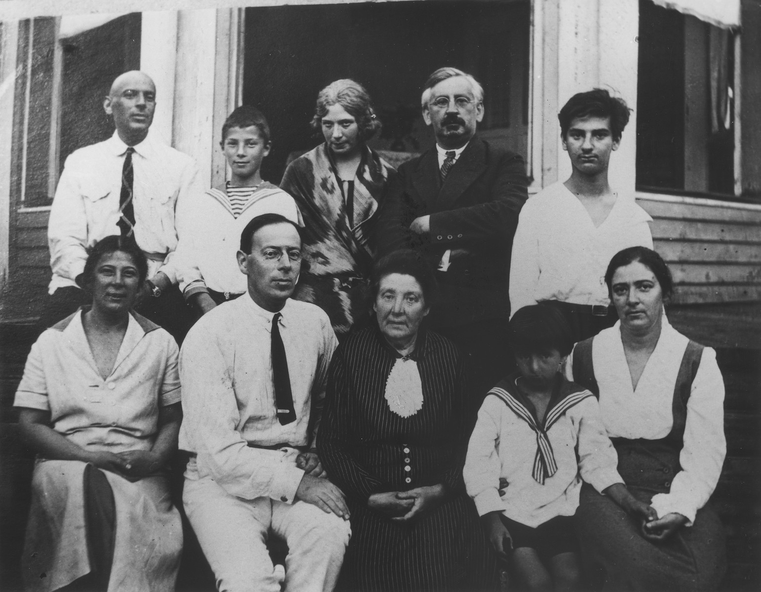 Group portrait of the Mikolaevsky family in front of their dacha in the village of Streina, a suburb of St. Petersburg.  Pictured standing in the back row (from left to right) are:  Sasha Mikolaevsky, Mark Magid, Emilia Mikolaevsky, Nathaniel Broido, and Alexander Mikolaevsky.  Sitting in the front row (from left to right) are: Maria Mikolaevsky Magid, her son Michael Magid, Fanya Mikolaevsky, Lev Broido, and Anna Mikolaevsky Broido.