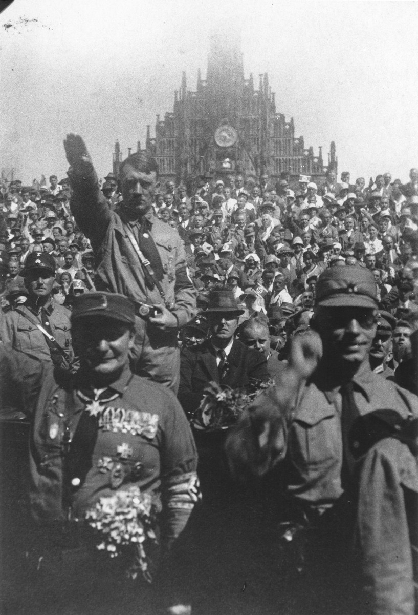 Standing amidst a large crowd, Adolf Hitler gives the Nazi salute during a Reichsparteitag (Reich Party Day) rally.   In front of him is Hermann Goering.
